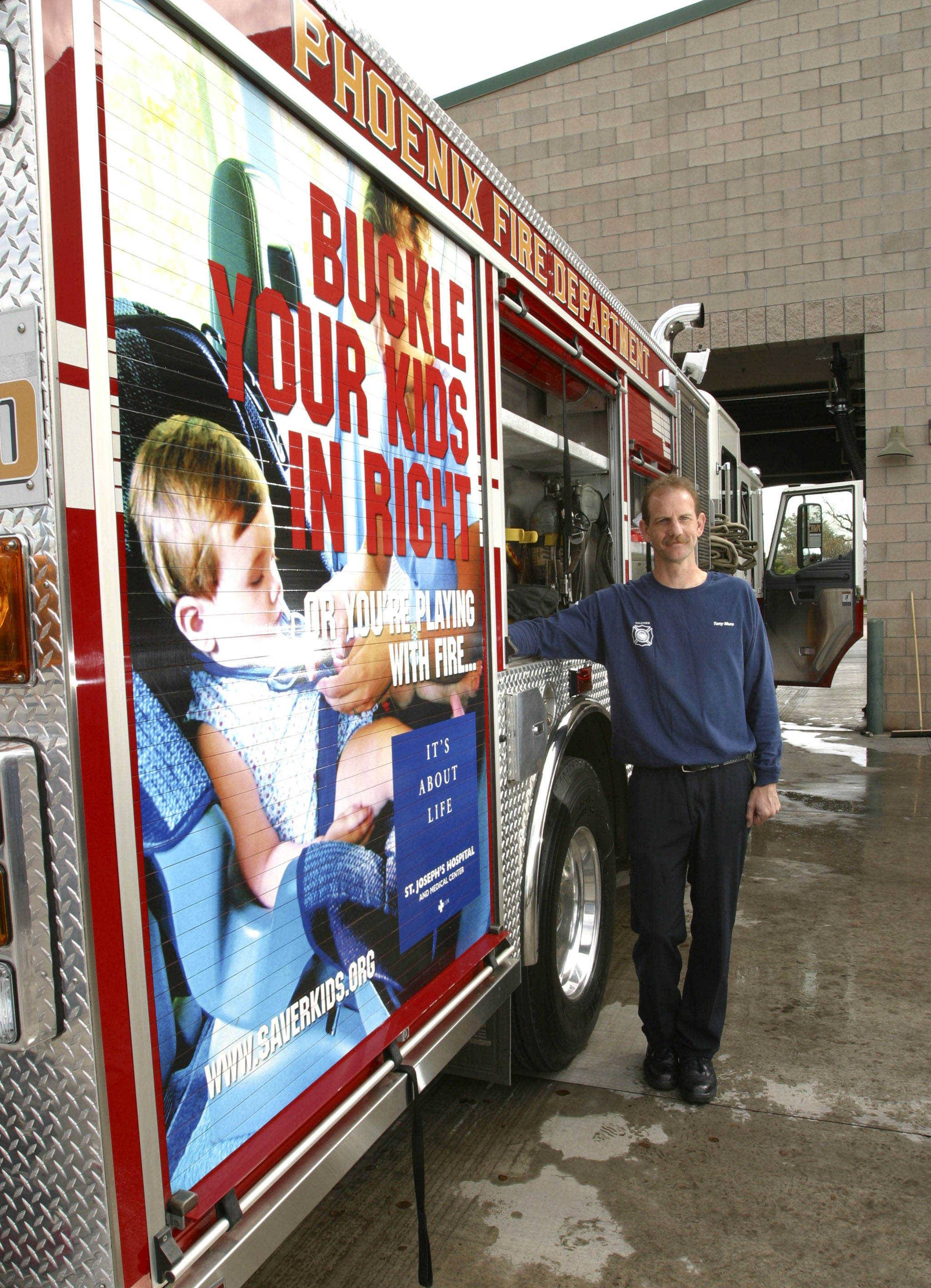 Phoenix, Ariz., Fire Department Captain Tony Mure of Station 30 shows off an ad on a fire engine. Ten fire trucks are carrying public safety messages about watching children around water and buckling up.