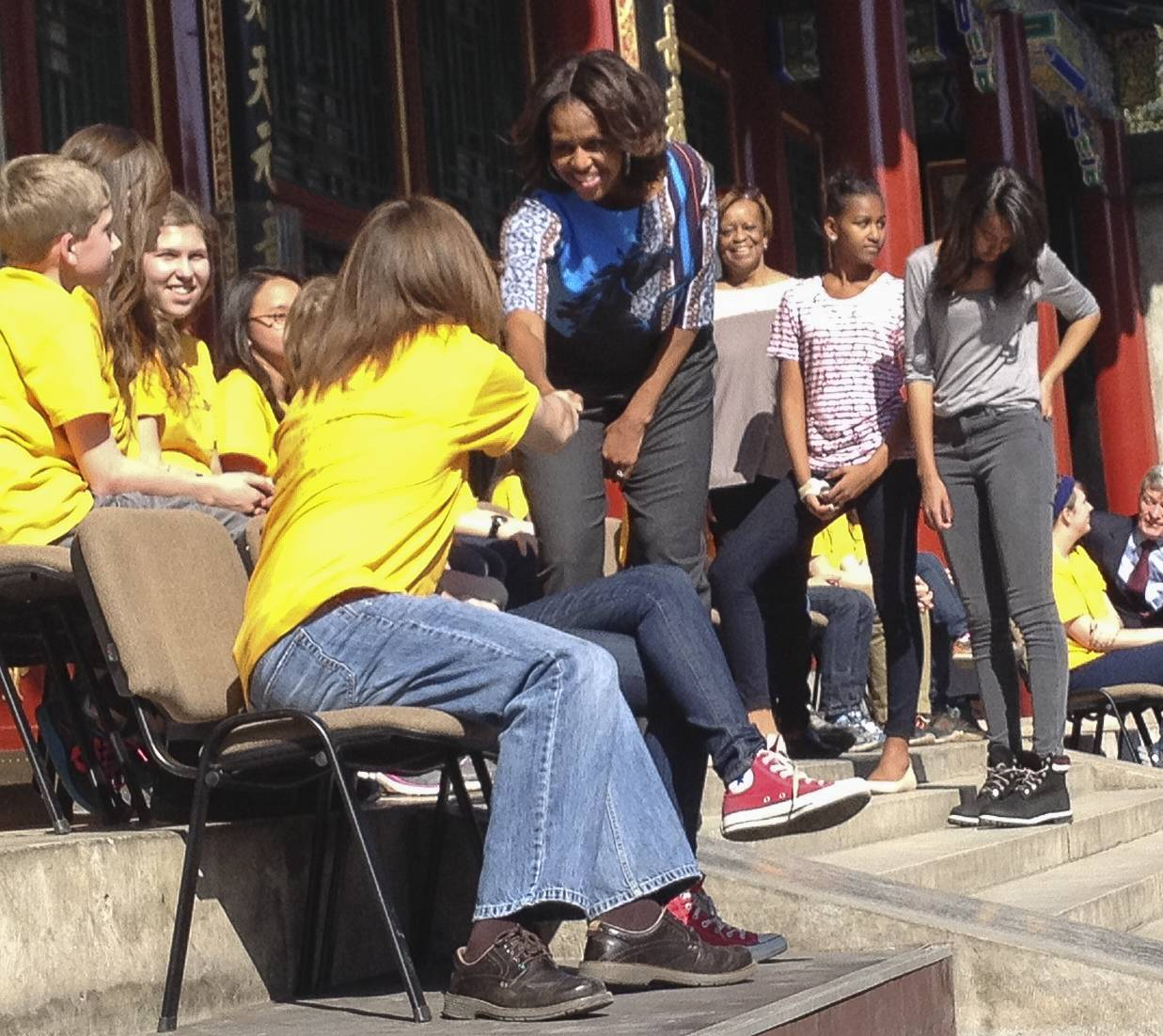 Arlington Heights middle-school students shake first lady Michelle Obama's hand as she enters the Garden of Virtue and Harmony in China.