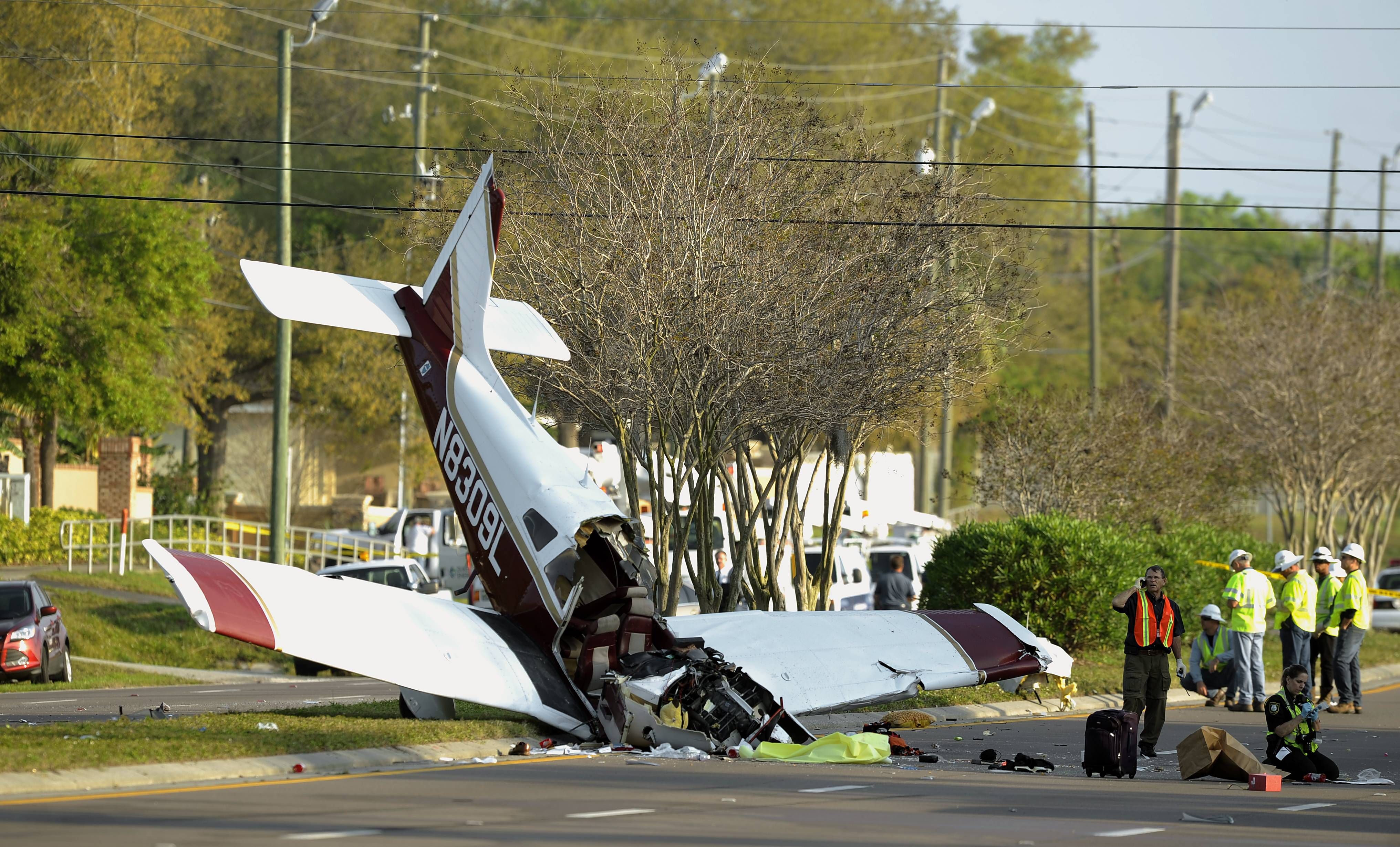 Investigators look at the wreckage of a small passenger plane which crashed early Saturday in Clearwater, Fla. Jeffrey Bronken, 53, of Round Lake was killed in the crash and Katherine Bronken, 15, and Keyana Linbo,15, were injured injured. According to the Clearwater Police Department, the aircraft came to a rest on the median of a six-lane street.