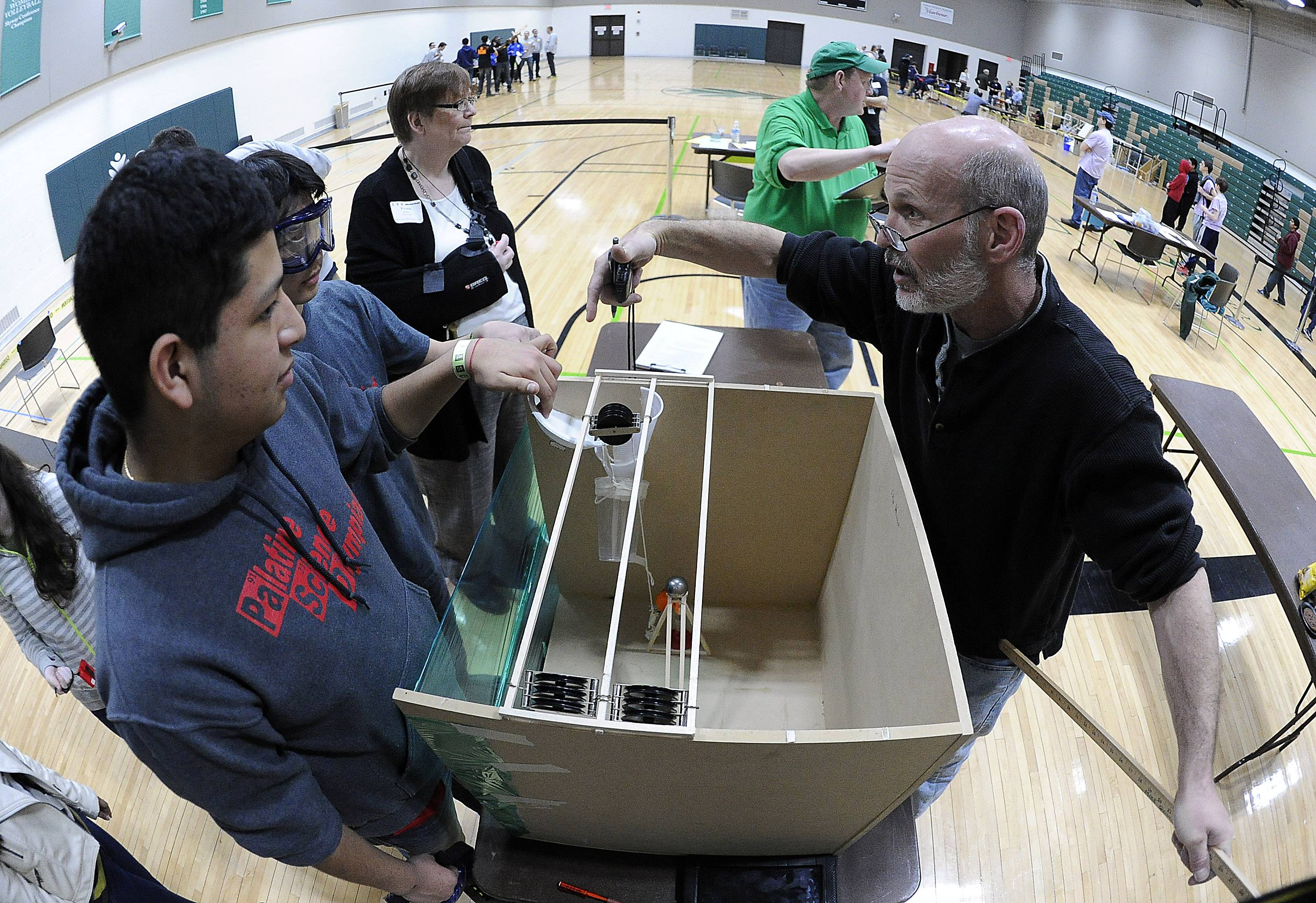 Giancarlo Rivera Moore and his partner Ryan Jannak-Huang, of Palatine High School, demonstrate their science project to judge Rory Wolfe in the Mission Possible event at the Science Olympiad at Oakton Community College in Des Plaines on Saturday.