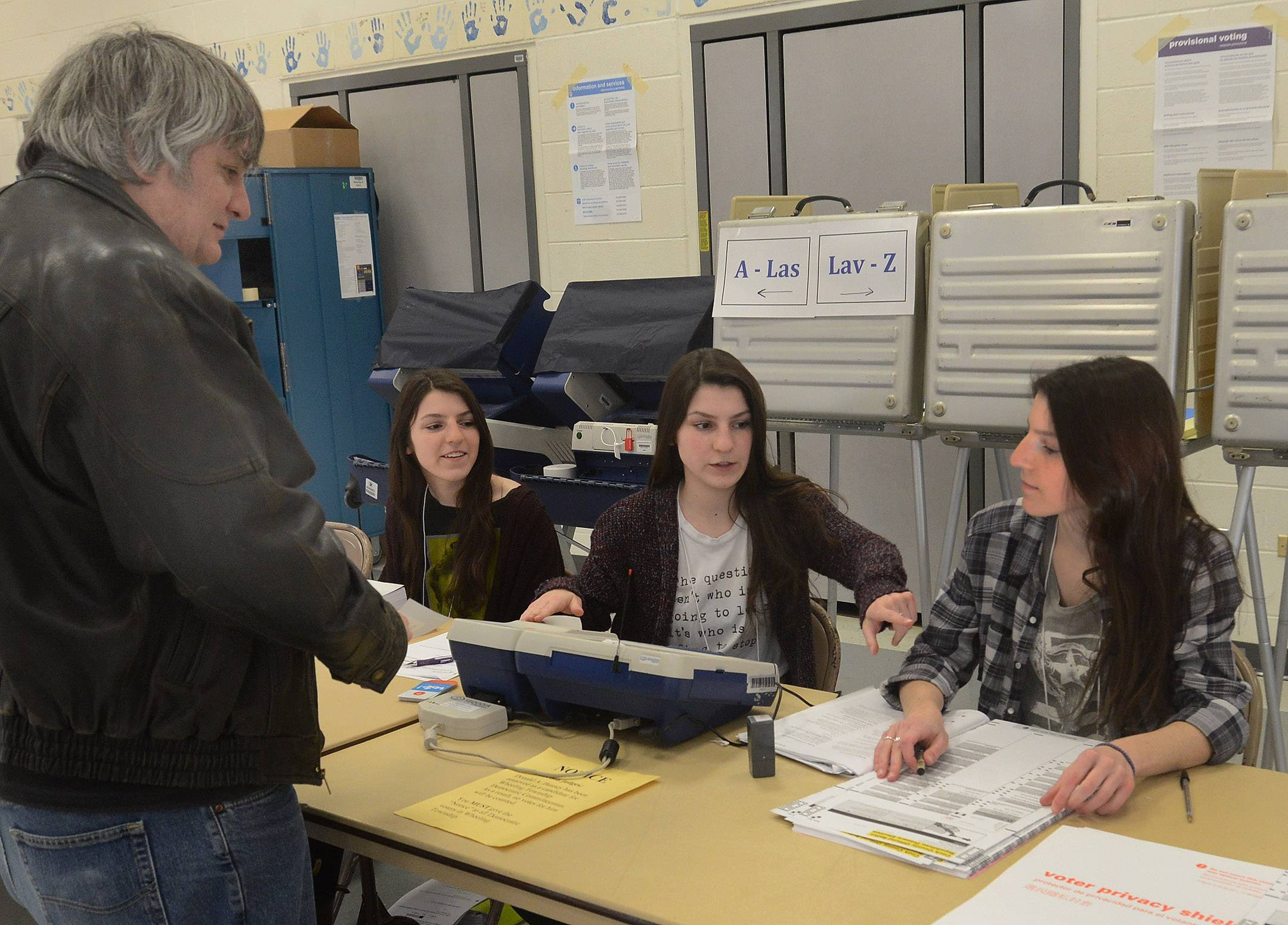 Triplets Frances, left, Theresa, and Mary Ponicki, right, issue a ballot to  Russel Butler of Arlington Heights Tuesday morning at the Riley School polling place in Arlington Heights.