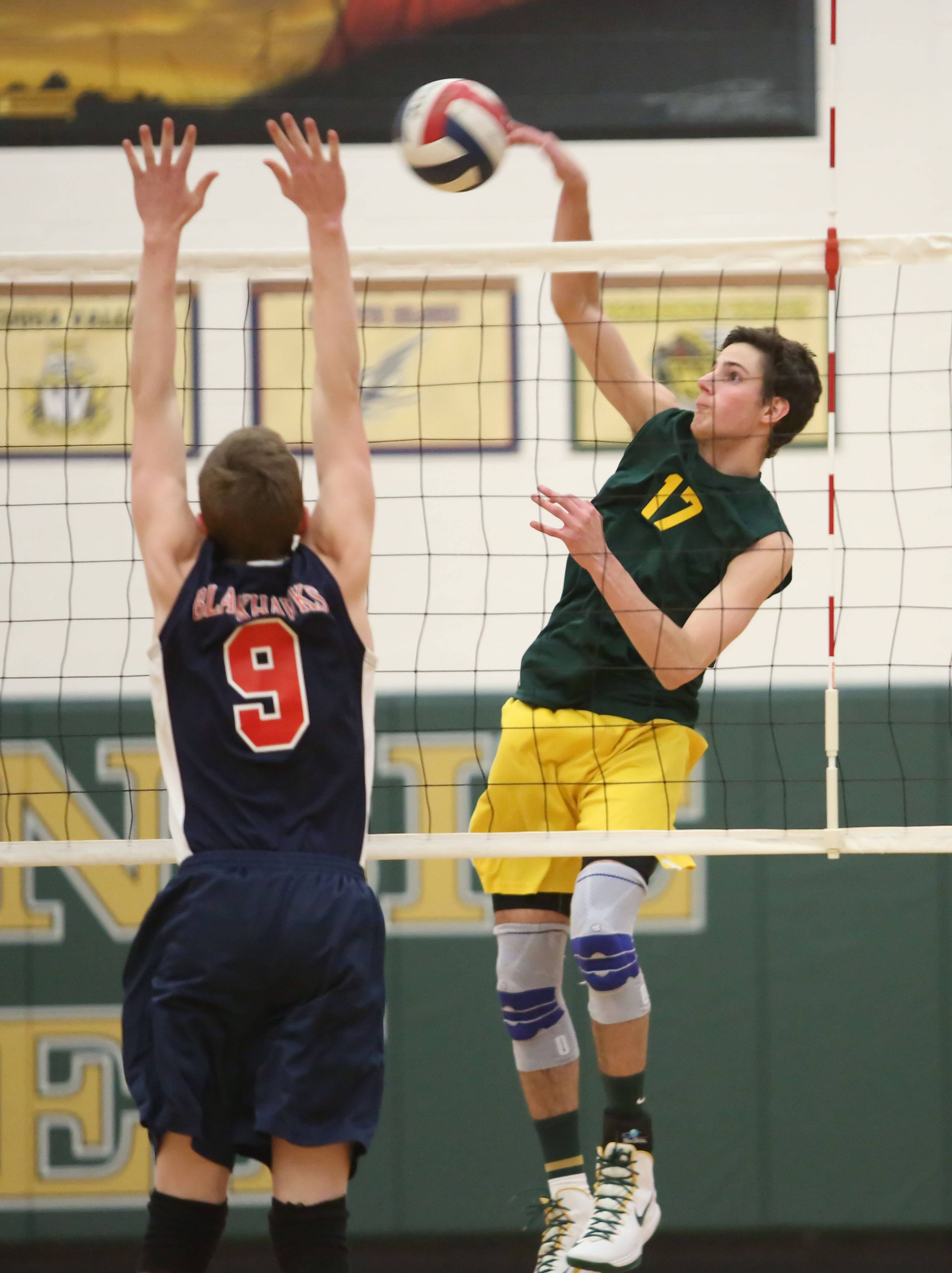 Waubonsie Valley's Michael Simmons, right, hits the ball as Adam Fitzgerald of West Aurora defends in boys volleyball action on Monday in Aurora.