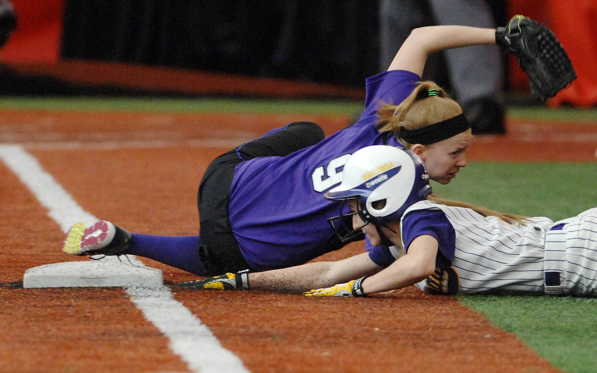 Wauconda's Kayla Wedl dives safely back into third after over-sliding the bag while Hampshire's Erin Doyle tries to reach back and make the tag during softball action Monday at The Dome in Rosemont.