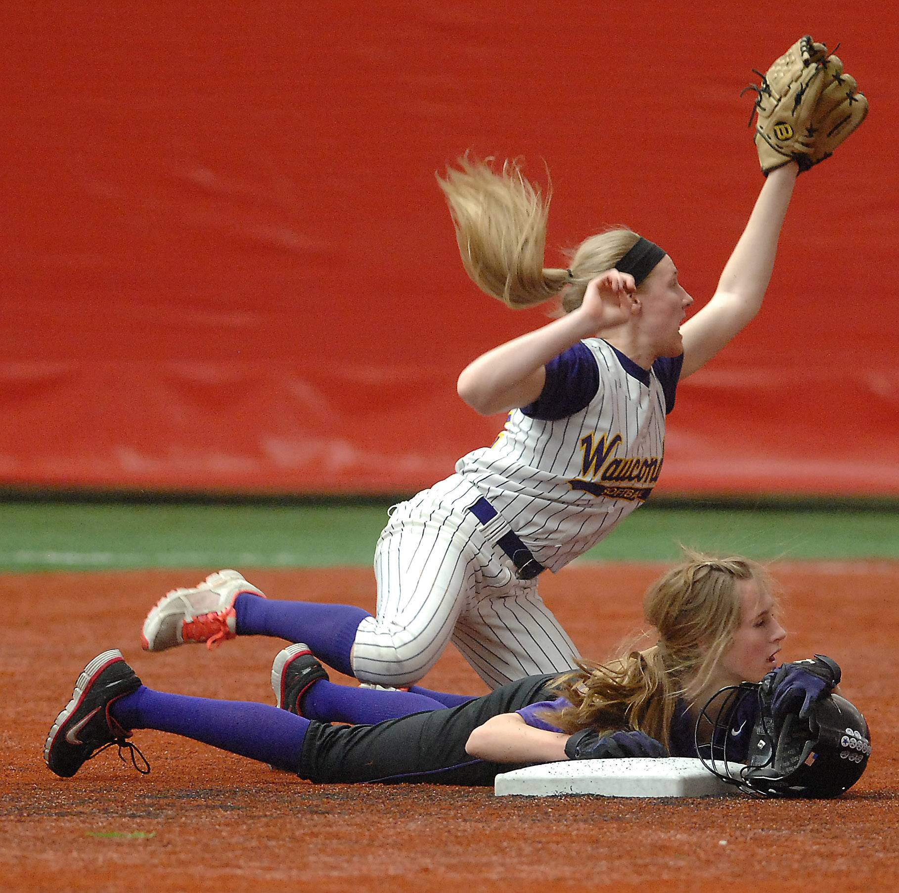Wauconda's Jenna Heck tumbles over Hampshire's Haley Widmayer as she slides safely into second during softball action Monday at The Dome in Rosemont.