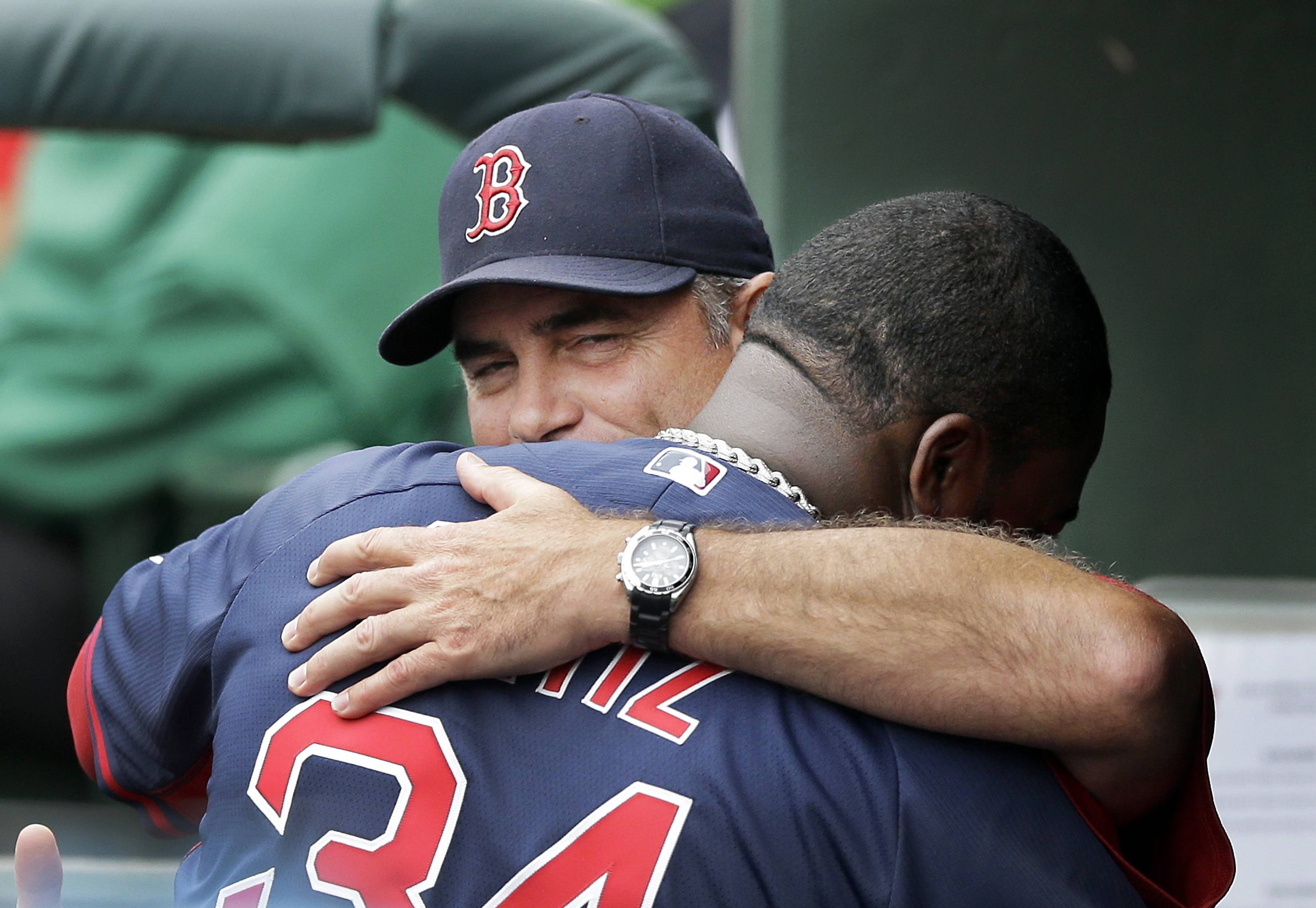 Boston Red Sox manager John Farrell hugs designated hitter David Ortiz, right, in the dugout before a spring exhibition baseball game against the Baltimore Orioles in Sarasota, Fla., Monday, March 24, 2014.