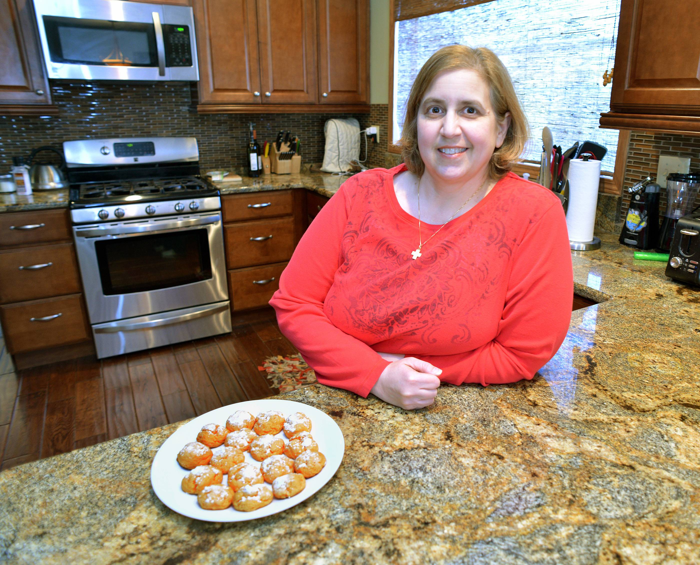 Christine Crabtree shows off a fresh batch of her orange dream cookies in her Winfield kitchen.