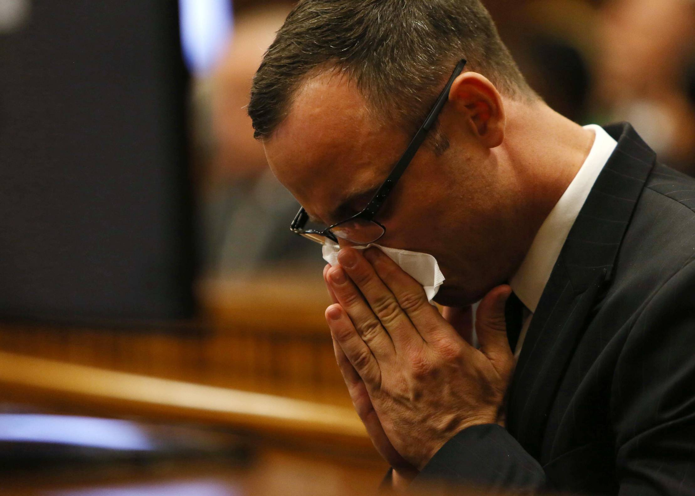 Oscar Pistorius reacts in the dock while listening to mobile phone evidence on exchanges of text messages between him as his girlfriend in court in Pretoria, South Africa, Tuesday. Pistorius is charged with the Valentines Day 2013 shooting death of his girlfriend Reeva Steenkamp.