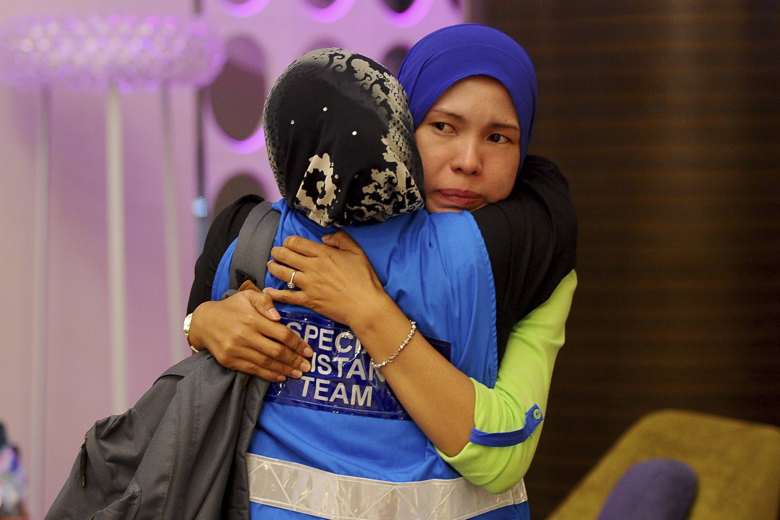 A family member, right, of passengers aboard a missing Malaysia Airlines plane is embraced Tuesday by a member of Special Assistance Team at a hotel in Putrajaya, Malaysia. Malaysia said Tuesday that it has narrowed the search for a downed jetliner to an area the size of Texas and Oklahoma in the southern Indian Ocean, while Australia said improved weather would allow the hunt for possible debris from the plane to resume.