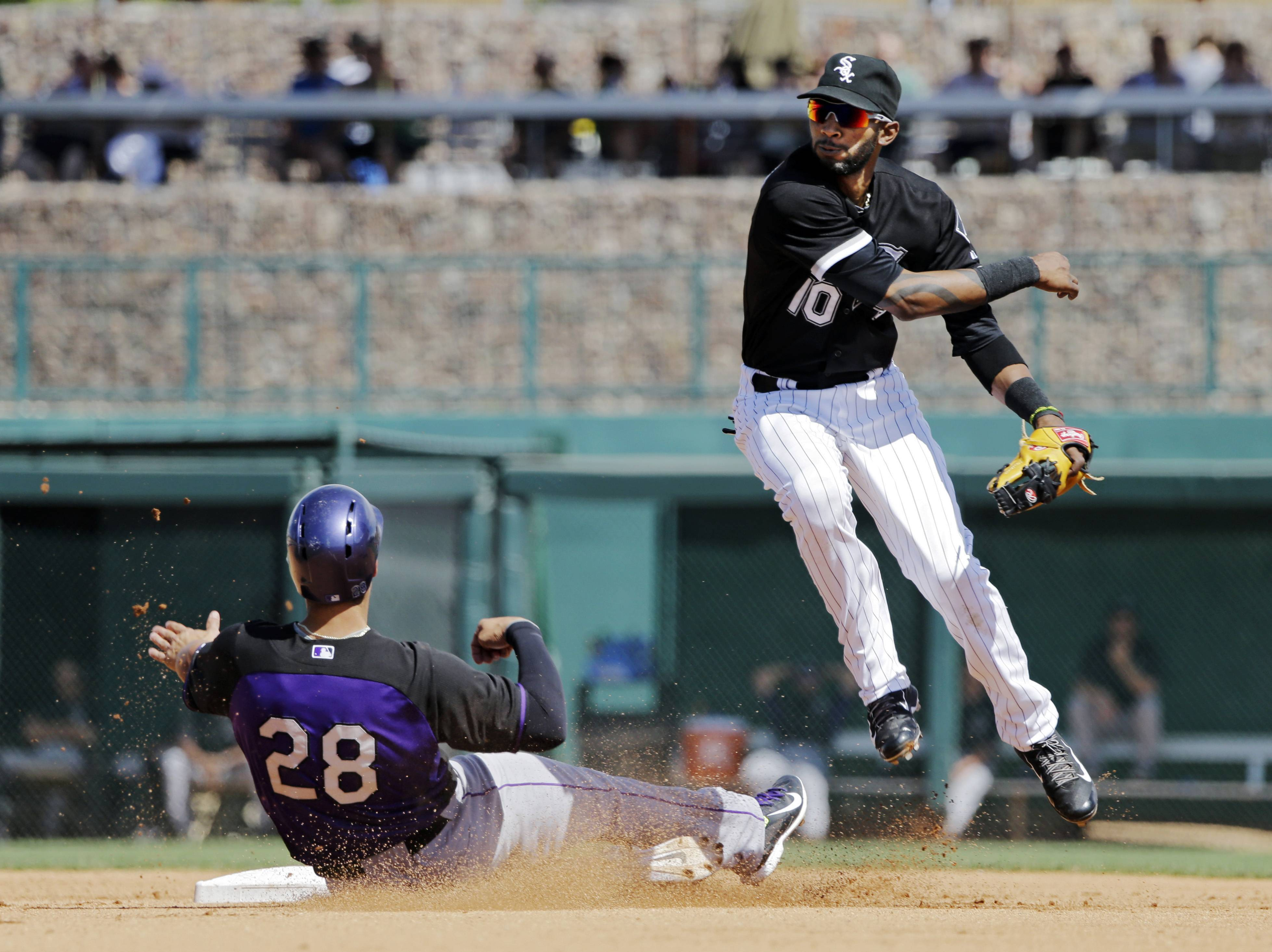 Chicago White Sox shortstop Alexei Ramirez avoids the slide of Colorado Rockies' Nolan Arenado (28) after relaying to first to complete a double play on Justin Morneau in the fourth inning of a spring exhibition baseball game Tuesday, March 25, 2014, in Glendale, Ariz. (AP Photo/Mark Duncan)