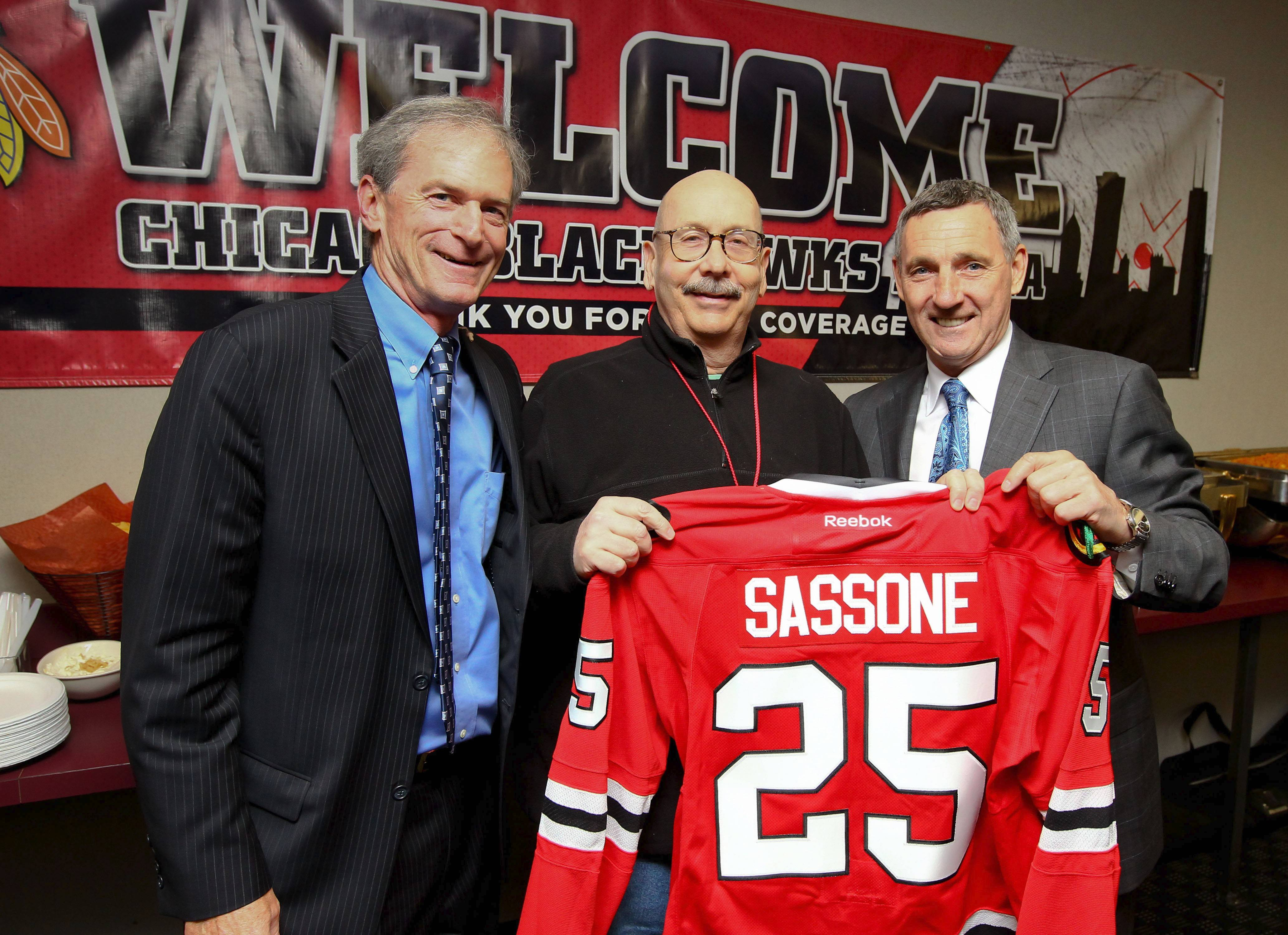 Near the end of the regular season in 2013, in honor of his 25 years of covering the team, Tim Sassone of the Daily Herald was presented with a Blackhawks jersey by veteran broadcaster Pat Foley, left, and hockey legend Denis Savard. Sassone died Tuesday at the age of 58.