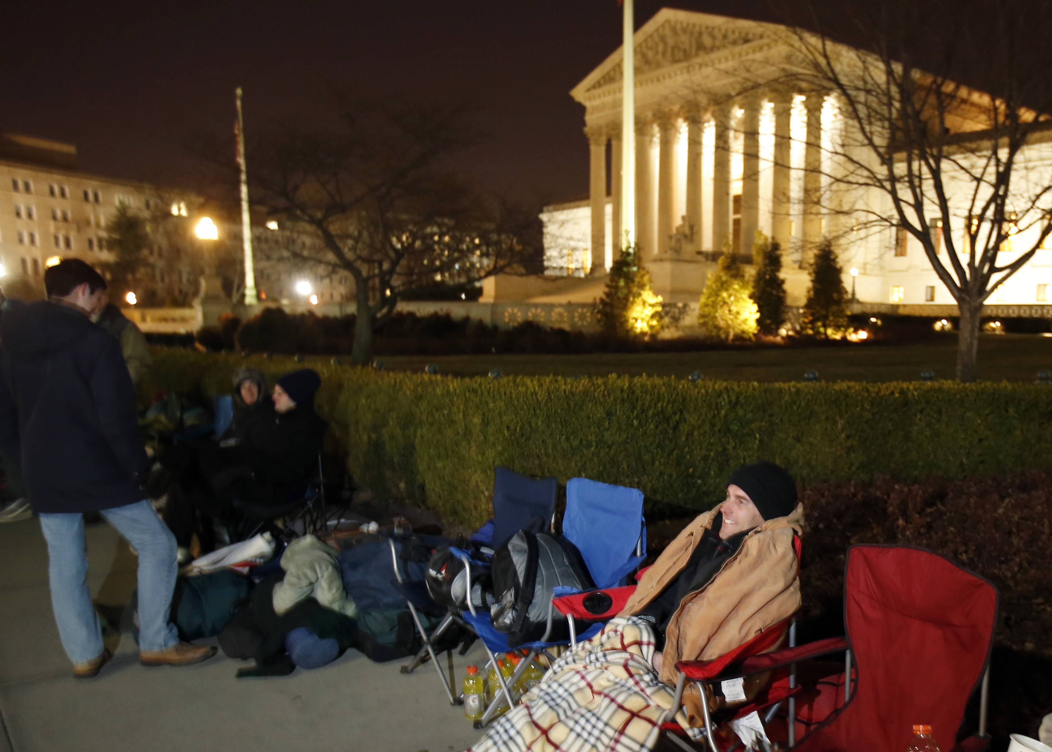 Jerome Weaver waits in line Monday in front of the Supreme Court in Washington. The Supreme Court is weighing whether corporations have religious rights that exempt them from part of the new health care law that requires coverage of birth control for employees at no extra charge.