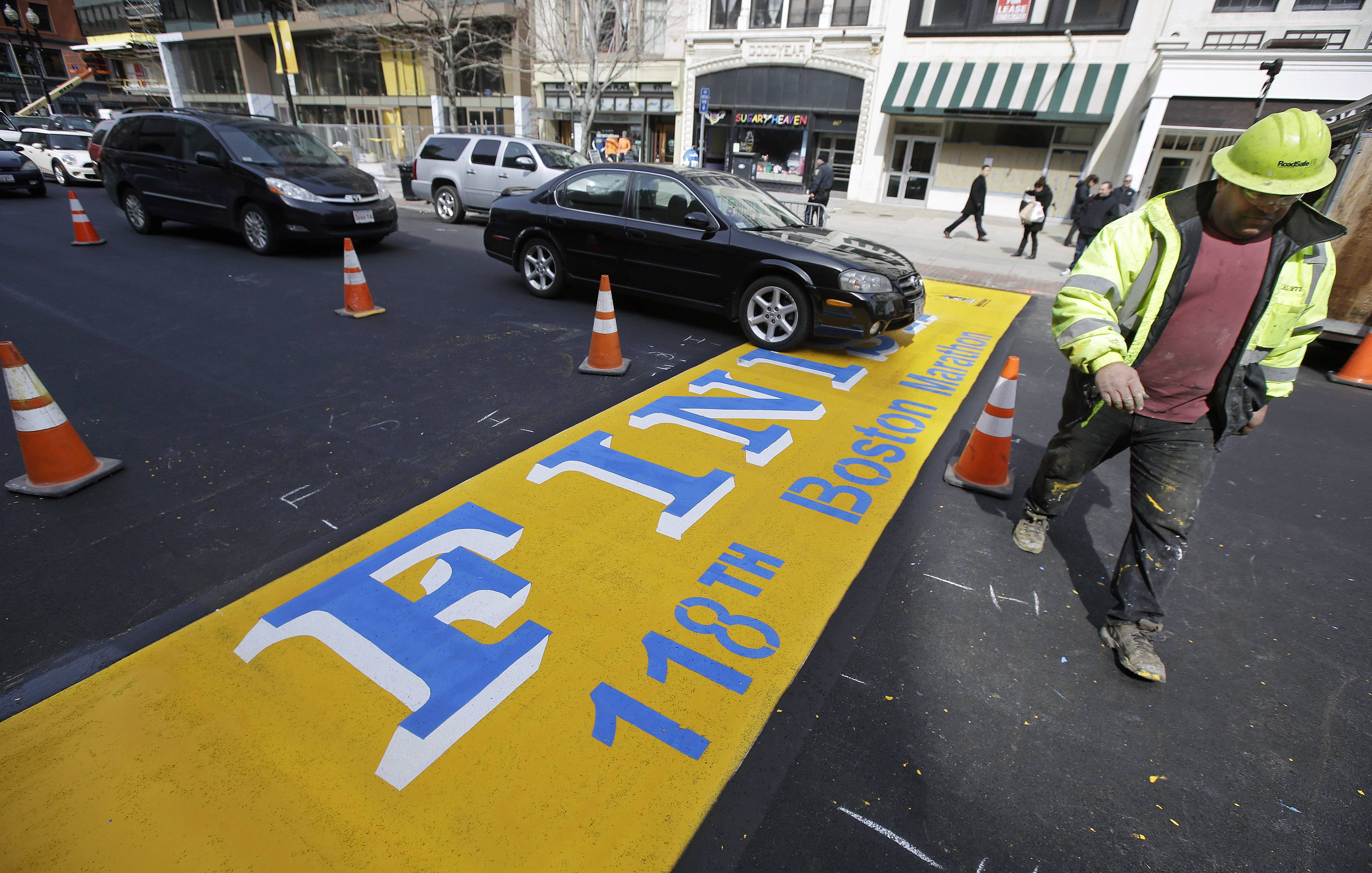 Eric House walks next to the Boston Marathon finish line while working on applying a fresh coat of paint on Boylston Street in Boston Tuesday. The 118th running of the Boston Marathon is scheduled for April 21.