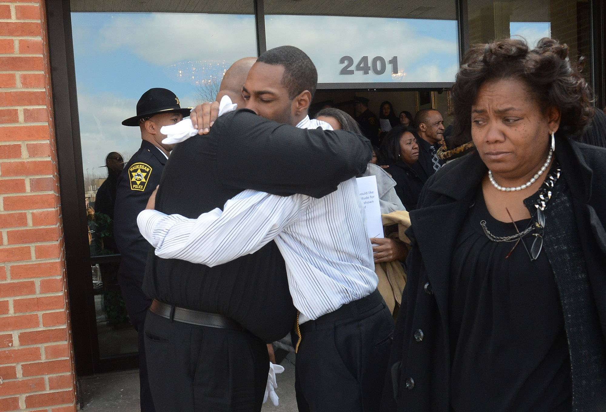 Demetri Frison-Green, right, consoles his father, Ossie Green Jr., after the funeral Tuesday for Artis Yancey, former Lake County coroner and Waukegan police chief. Frison-Green was Yancey's great nephew and Green Jr. was Yancey's nephew.