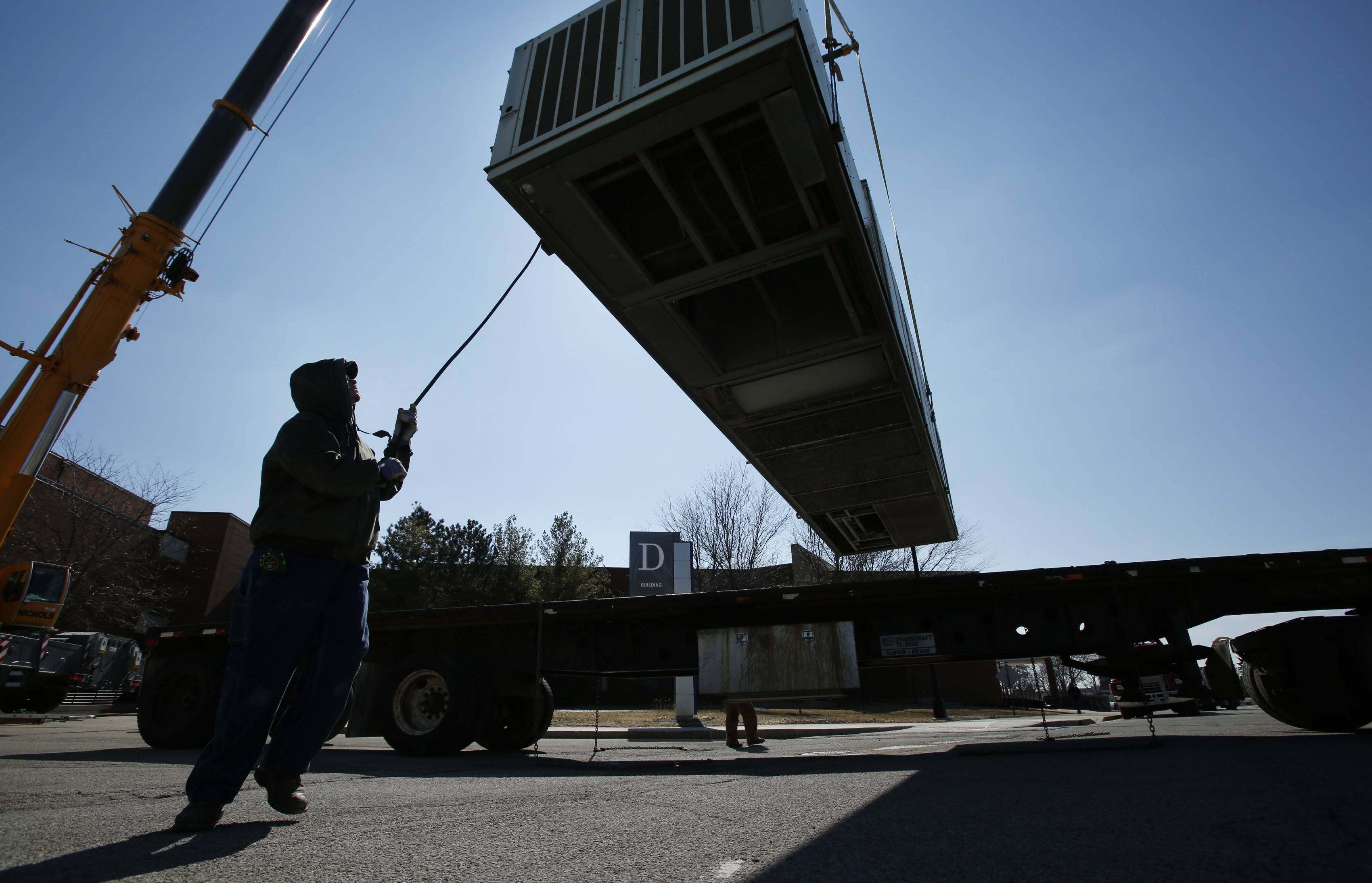 A massive air conditioning unit is positioned by Bill Wroblewski of Romeoville.