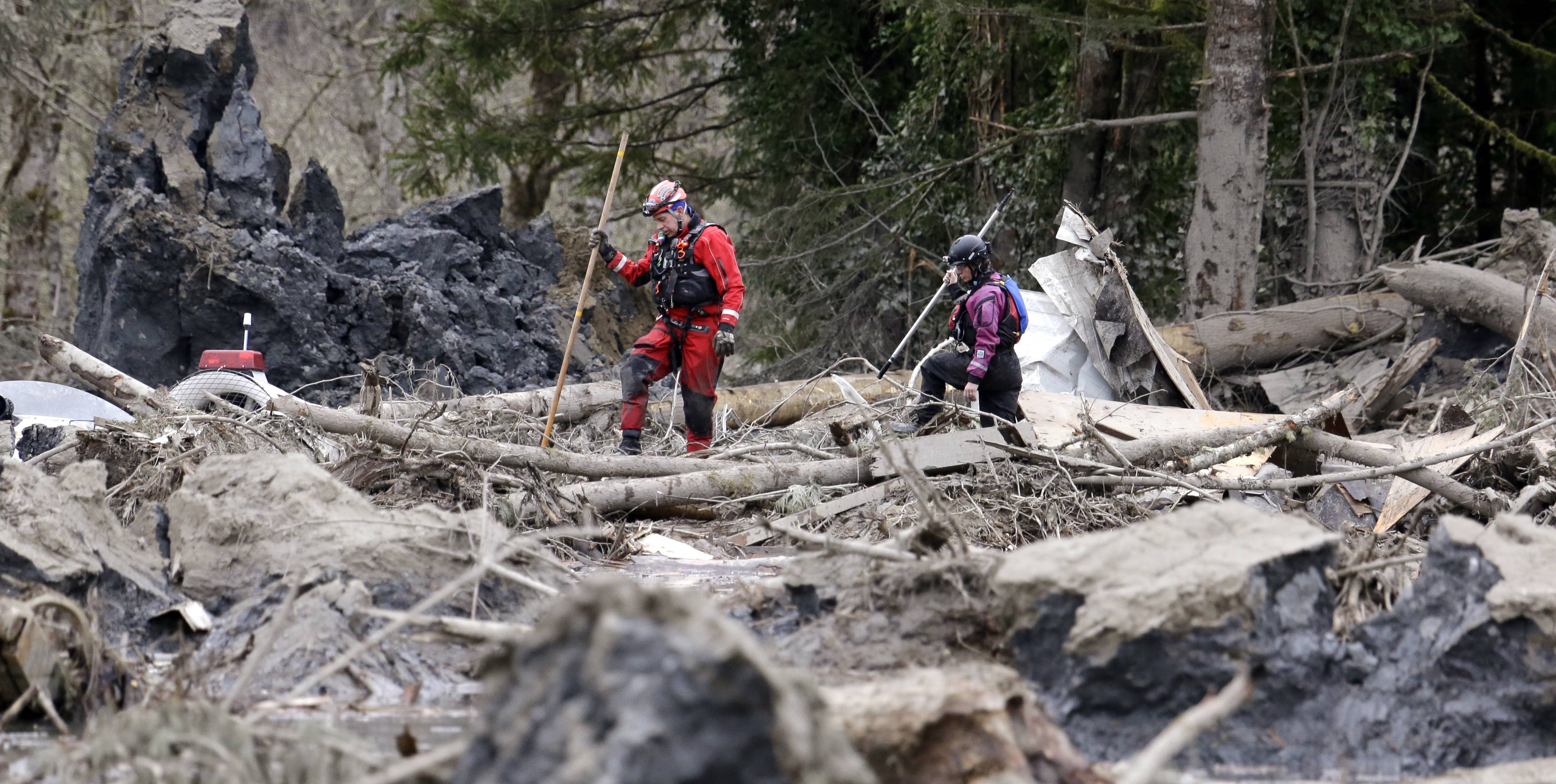 Searchers look through debris from a deadly mudslide Tuesday in Oso, Wash. At least 16 people were killed in the 1-square-mile slide that hit in a rural area about 55 miles northeast of Seattle on Saturday. Several people also were critically injured, and homes were destroyed.