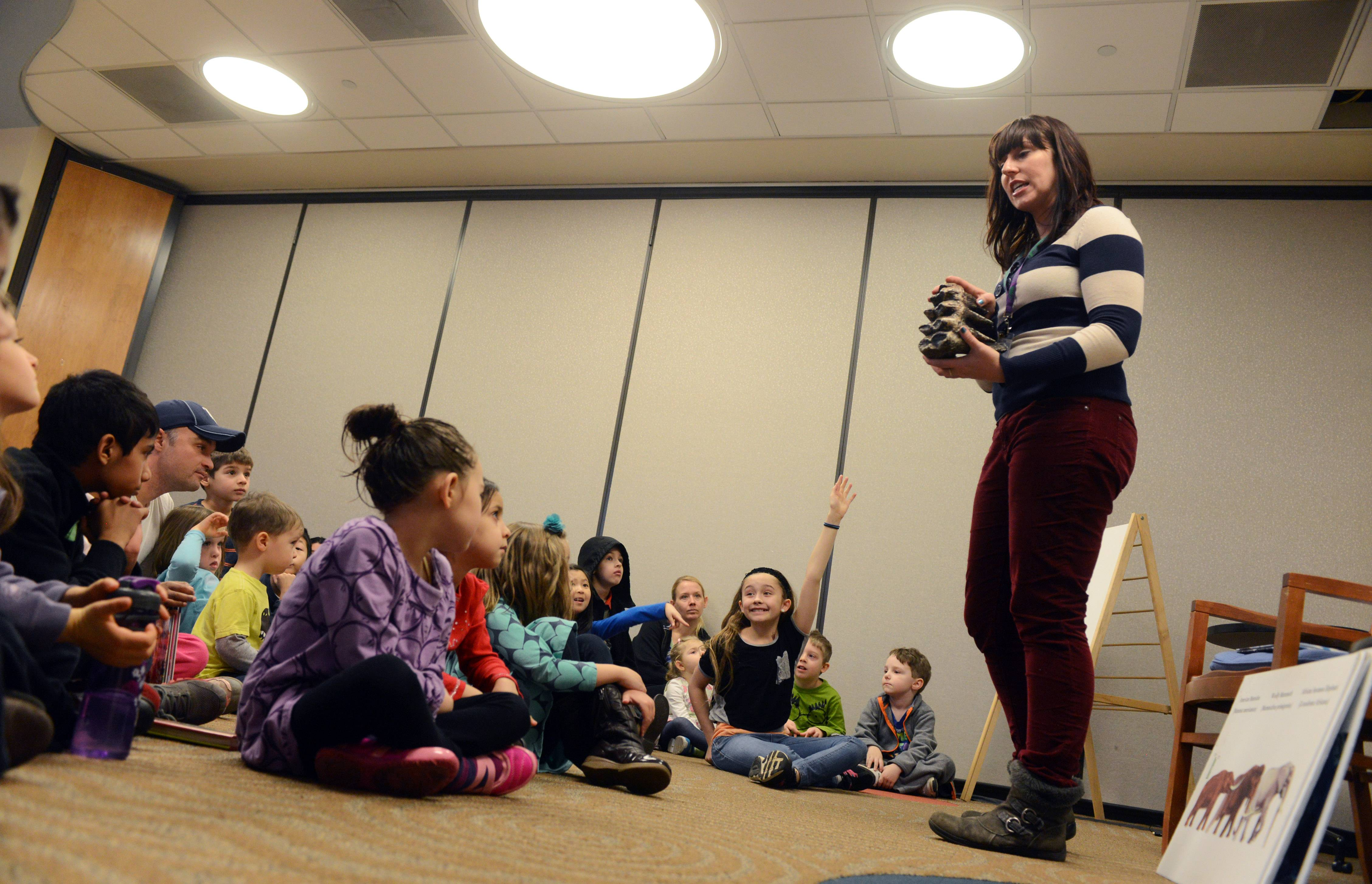 Lake County Discovery Museum educator Nicole Stocker shows a fossil cast of a mastodon tooth to kids participating in the Mighty Mastodons program Tuesday at Ela Area Public Library in Lake Zurich.