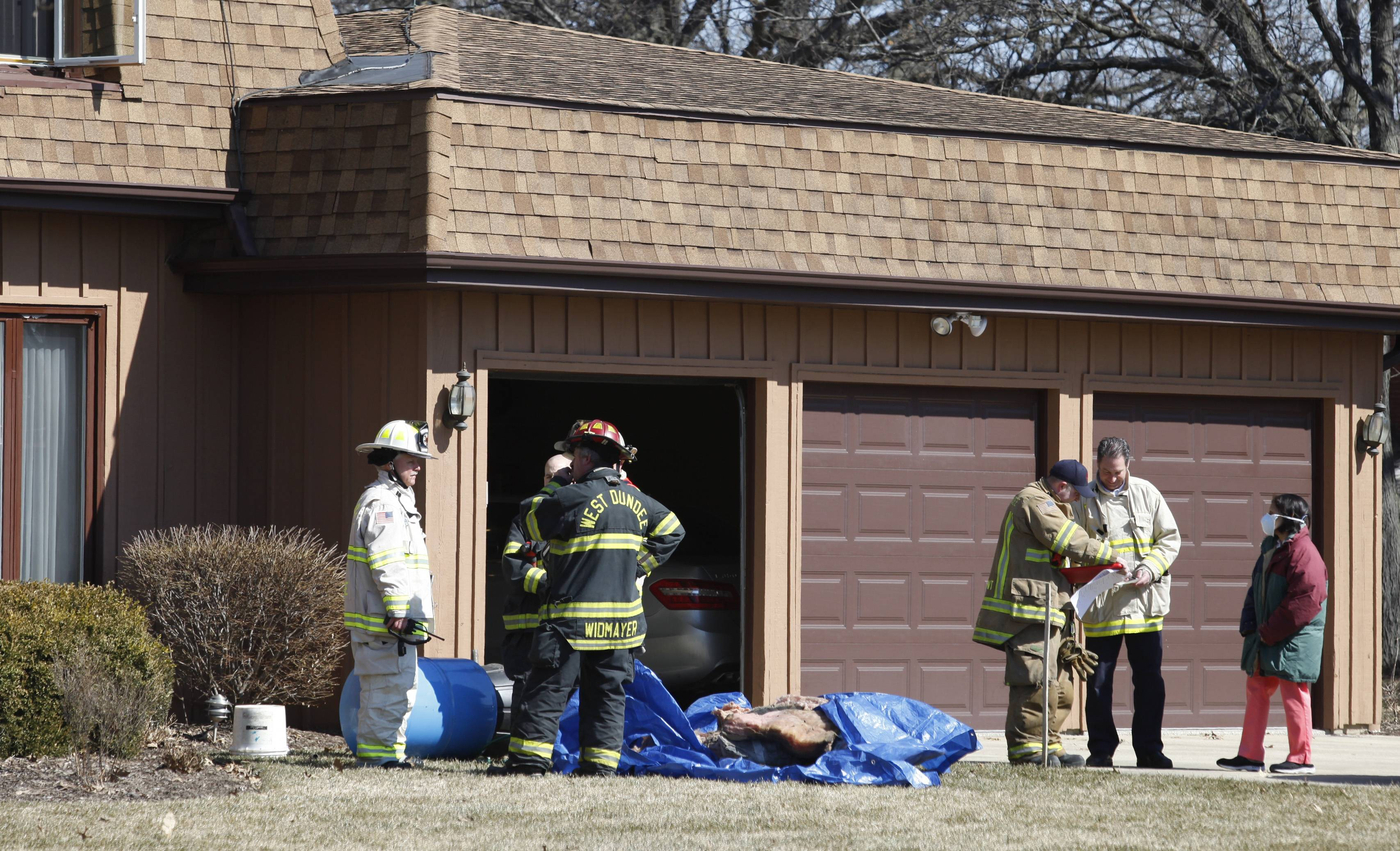 Firefighters from Rutland-Dundee and West Dundee fire departments discuss the situation outside a home along Frontenac Drive in West Dundee Monday morning after a small explosion sent two plumbing contractors to the hospital with minor injuries.