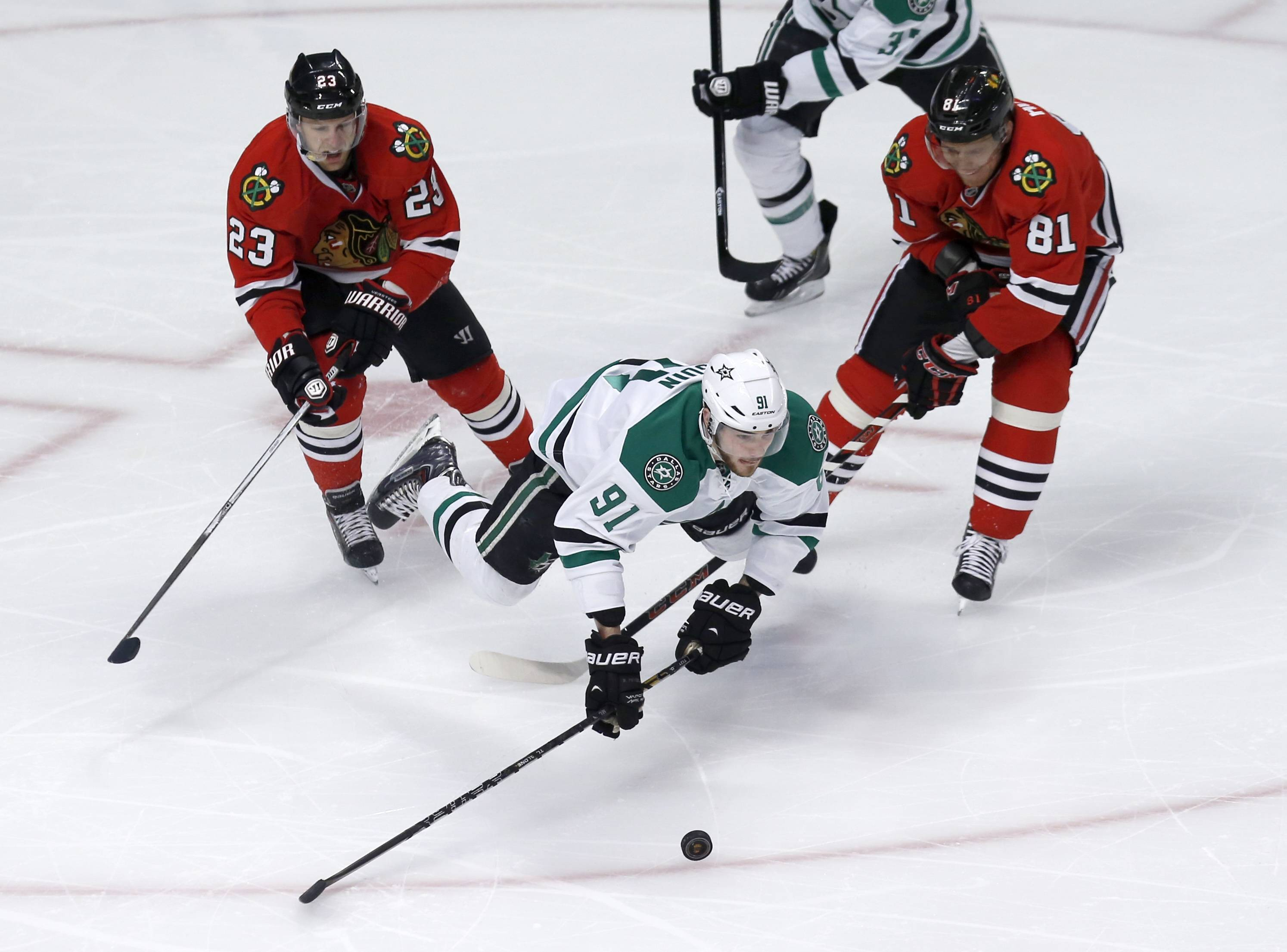 Dallas Stars center Tyler Seguin (91) falls to the ice between Chicago Blackhawks right wing Kris Versteeg (23) and Marian Hossa (81) during Tuesday night's game at the United Center.