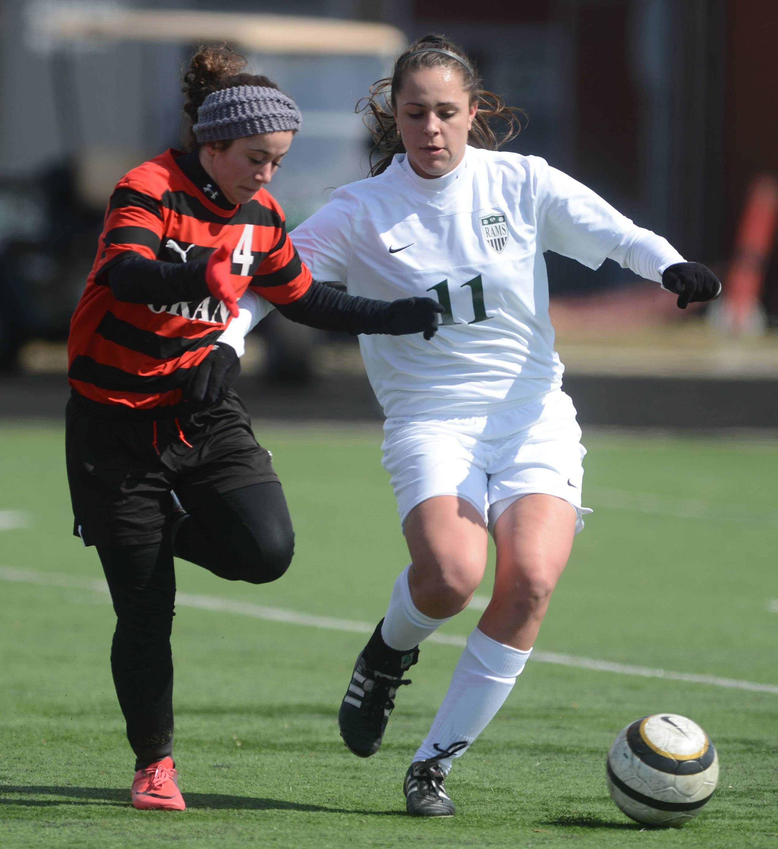 Grant's Nina Deligio (4) chases down the loose ball with Grayslake Central's Carson Sparkman during Tuesday's soccer game in Grayslake.