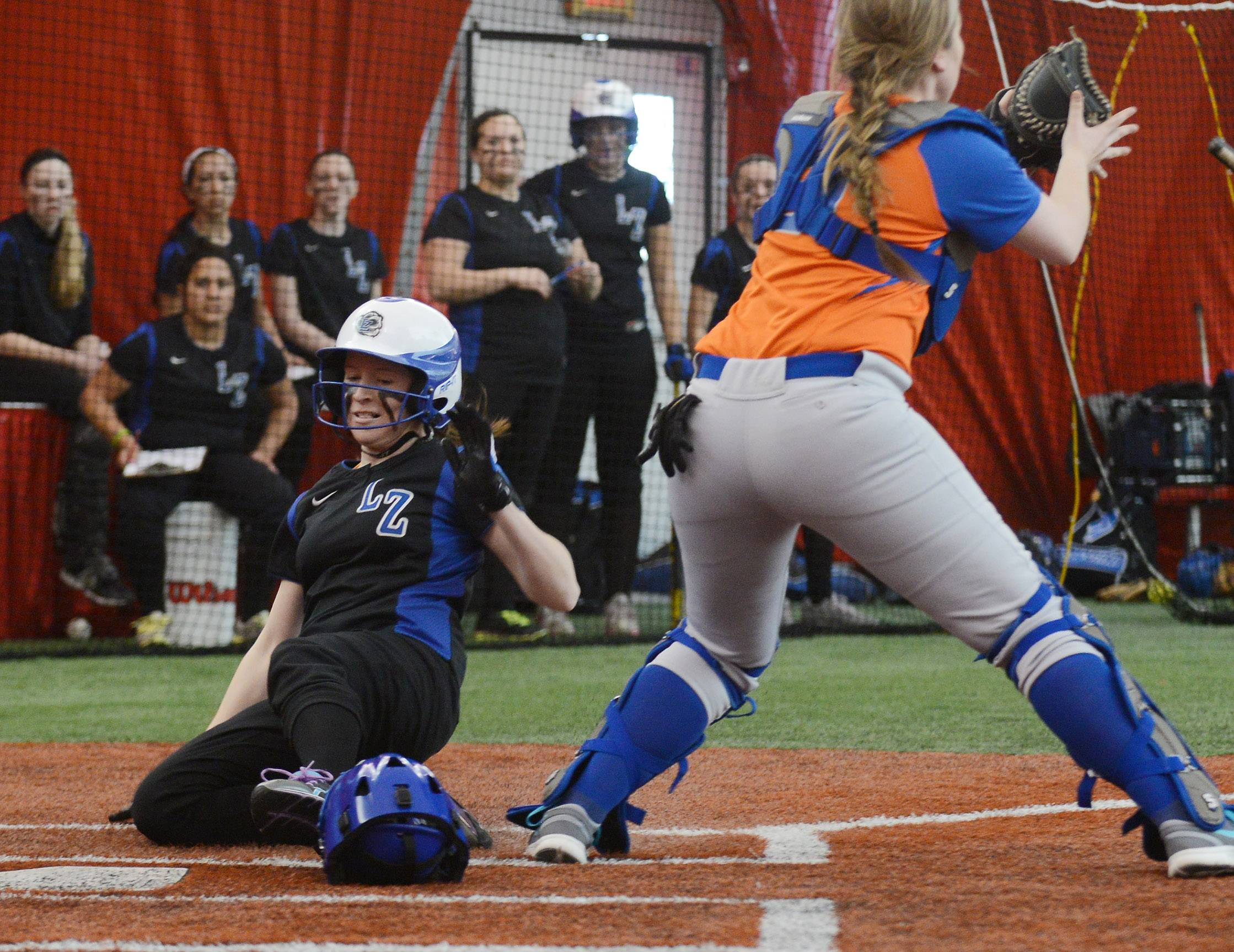 Lake Zurich's Brittney Pettinger slides safely into home as Hoffman Estates catcher Kaileen Hendle takes the late throw during softball action Tuesday in Rosemont.