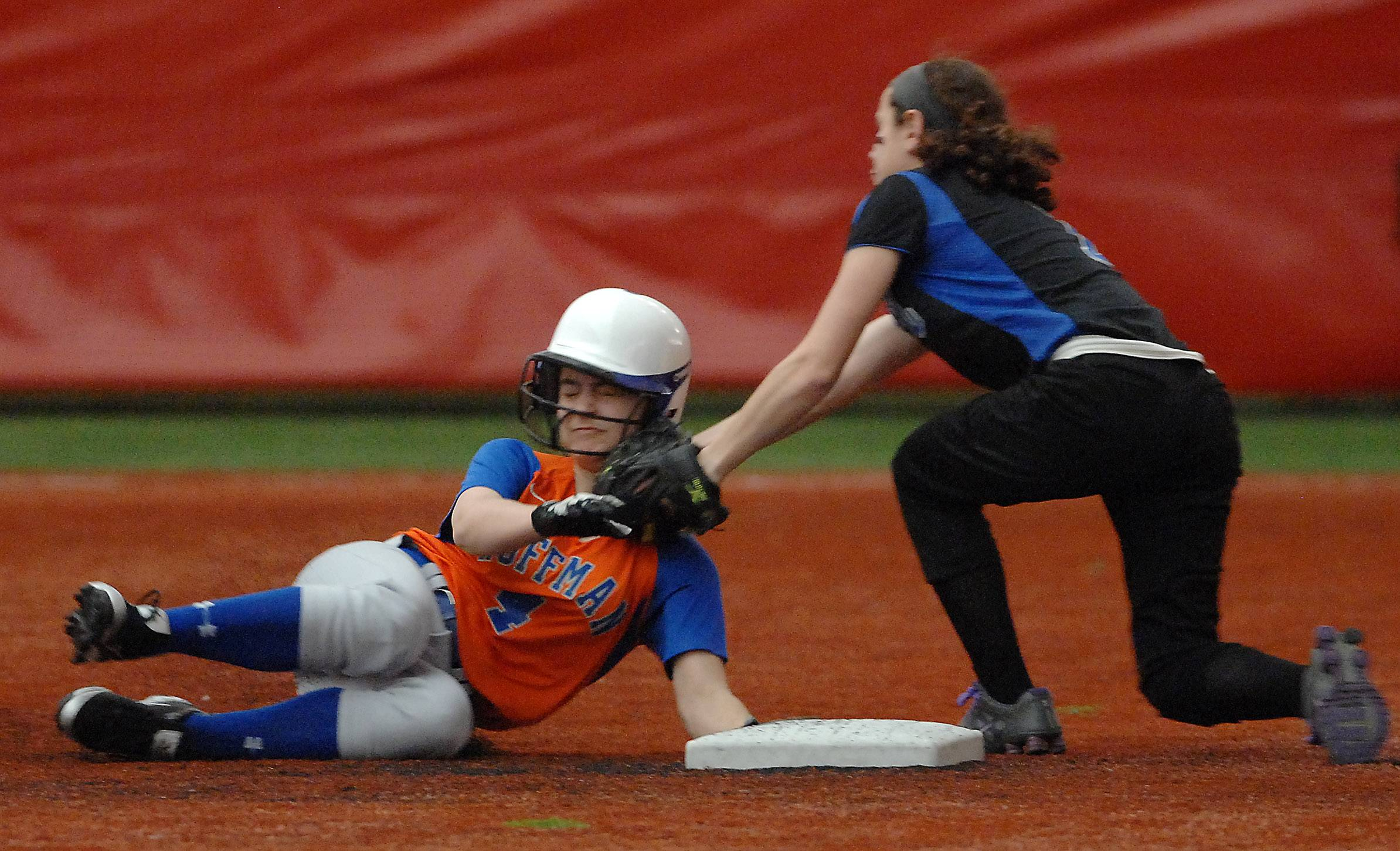 Brynn Connelly of Hoffman Estates slides safely in under the tag of Lake Zurich's Maddie Minneci during softball action Tuesday in Rosemont.