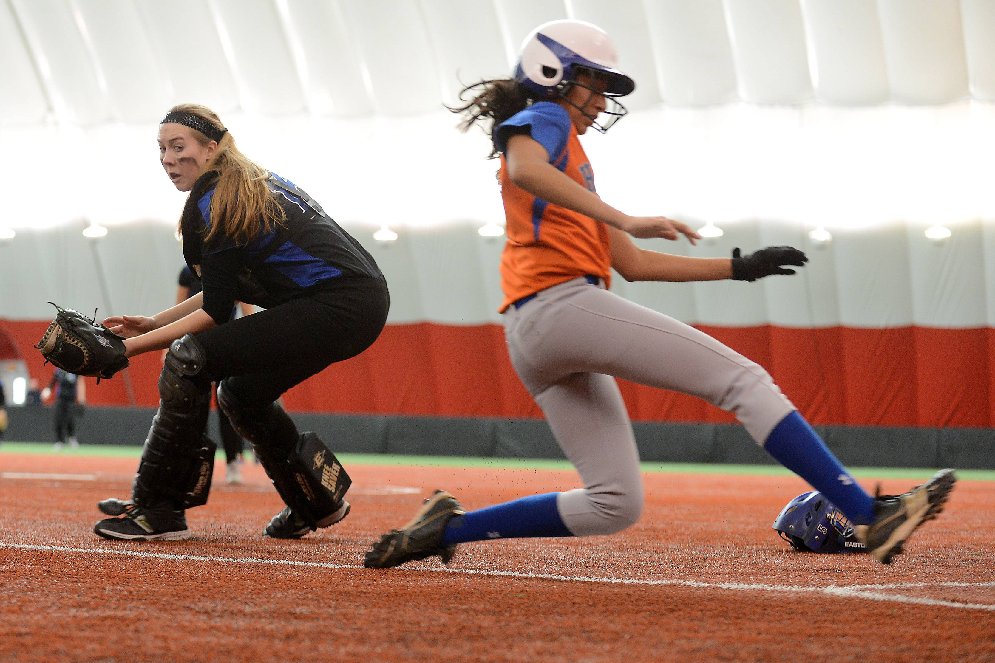 Kajal Dalal of Hoffman Estates slides safely into home as Lake Zurich catcher Amanda Guercio tries to wheel and make the tag during softball action Tuesday in Rosemont.