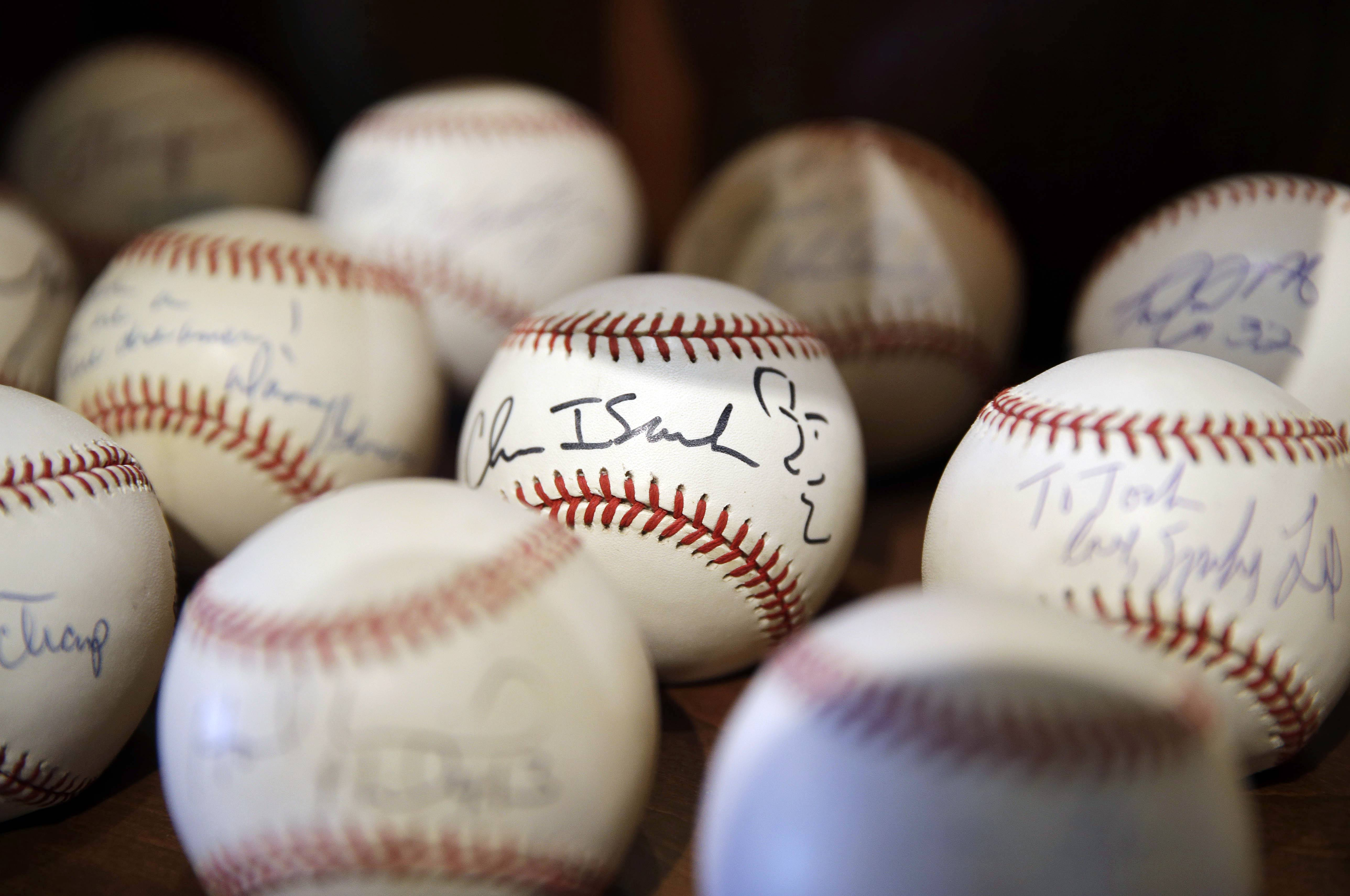 In this March 13, 2014 photo, a signed baseball with a self-portrait by rock musician Chris Isaak is shown in Dusty Baker's collection at his home in Granite Bay, Calif. Out of uniform for the first time since taking 2007 off between managerial jobs with the Cubs and Reds, Baker is not slowing down much from his pressure-packed days in the dugout.