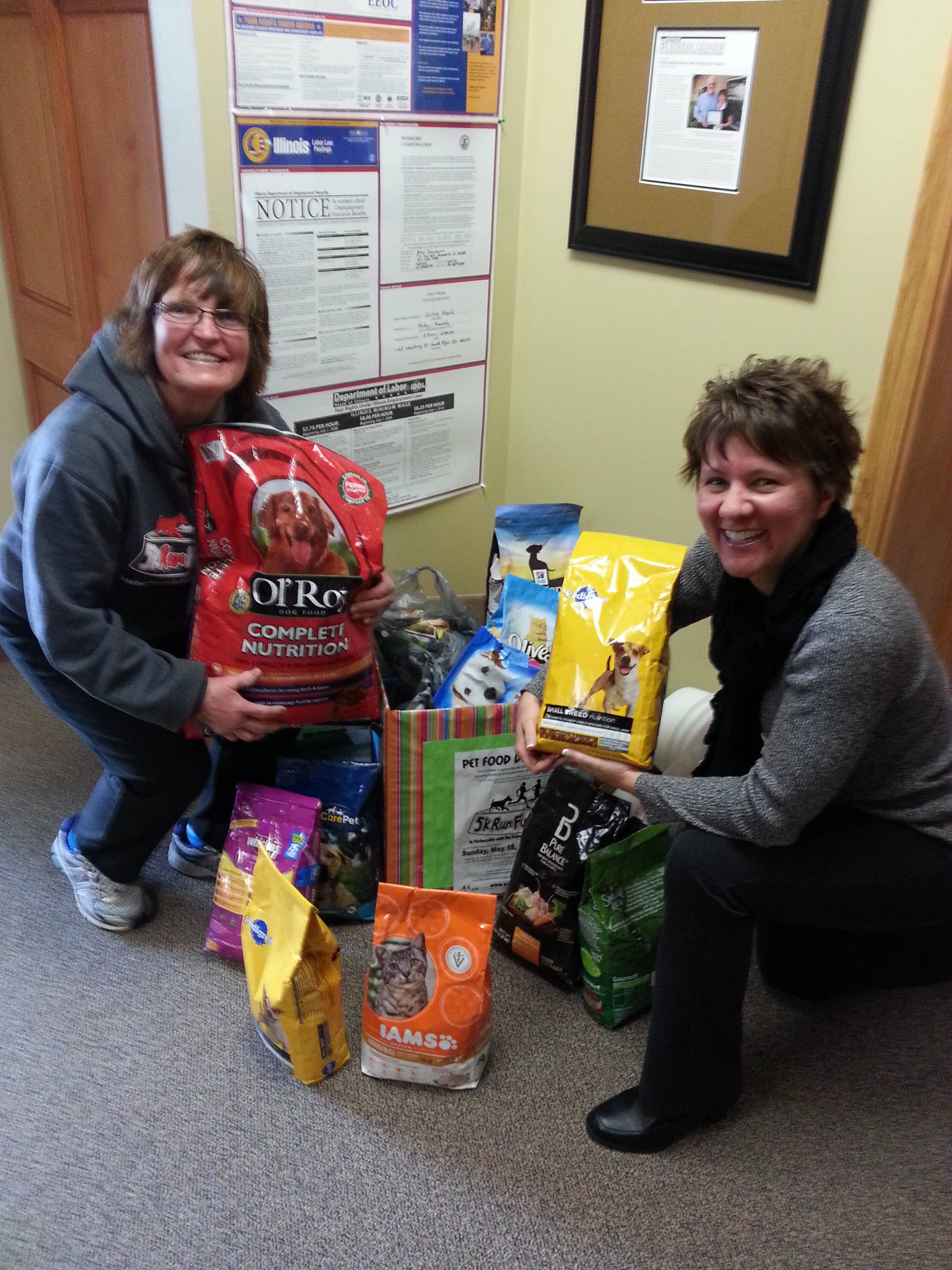 Sara Johnson, a caregiver for Visiting Angels and representative for RunFurShelter, along with Arlene Petersen, owner of Visiting Angels, show off some of the pet food collected.