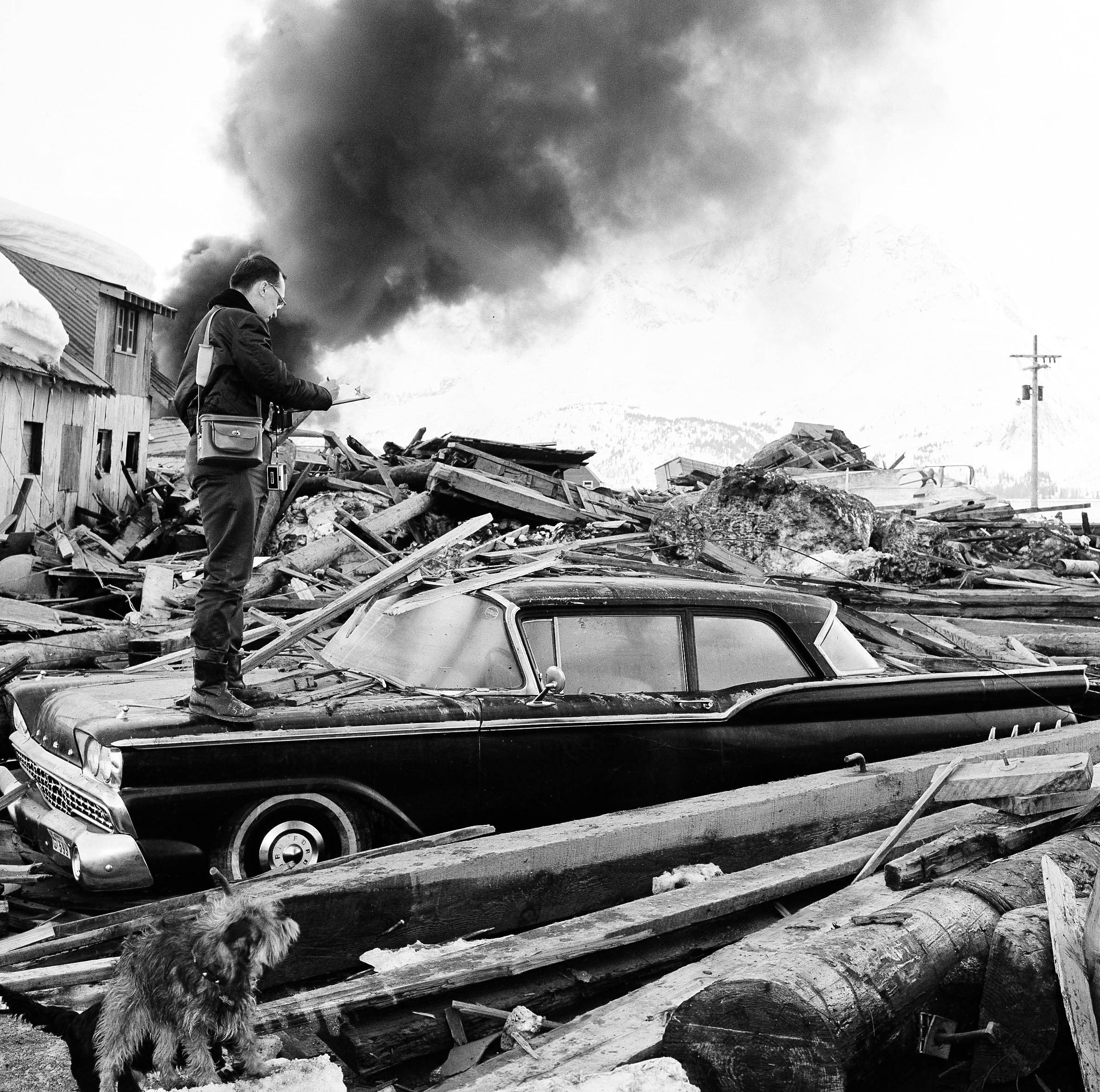 ASSOCIATED PRESS In this March 29, 1964, file photo, a photographer looks over wreckage as smoke rises in the background from burning oil storage tanks at Valdez, Alaska. The city was hit hard by the earthquake that demolished some of Alaska's most picturesque and largest cities.