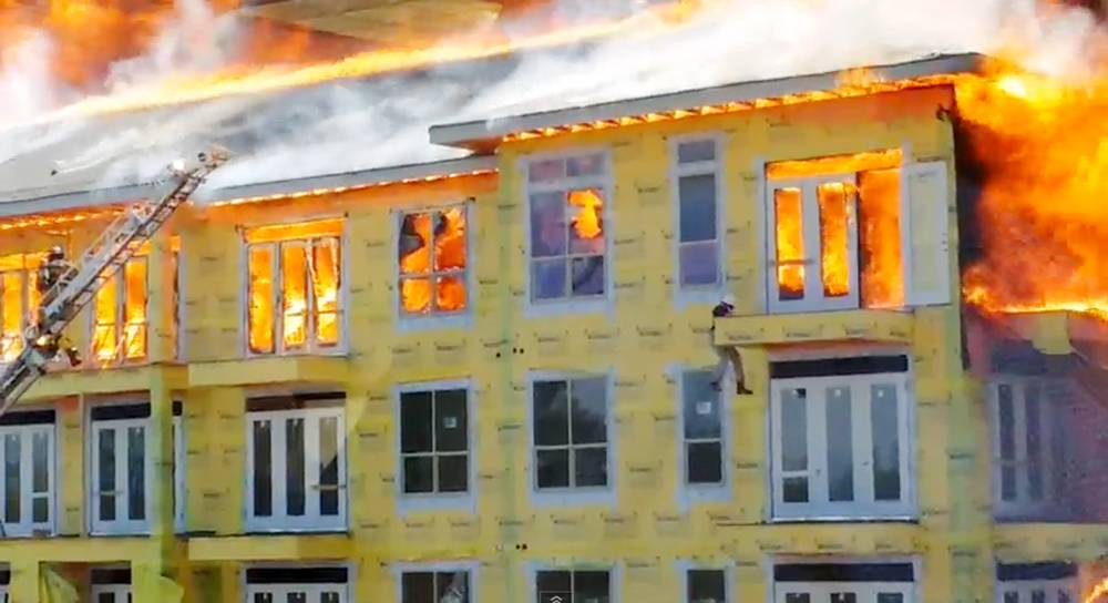 In this image taken from video provided by Karen Jones, a worker lowers himself from a fifth floor balcony before swinging down to the one below as firefighters battle a five-alarm fire at a construction site Tuesday, March 25, 2014, in Houston.