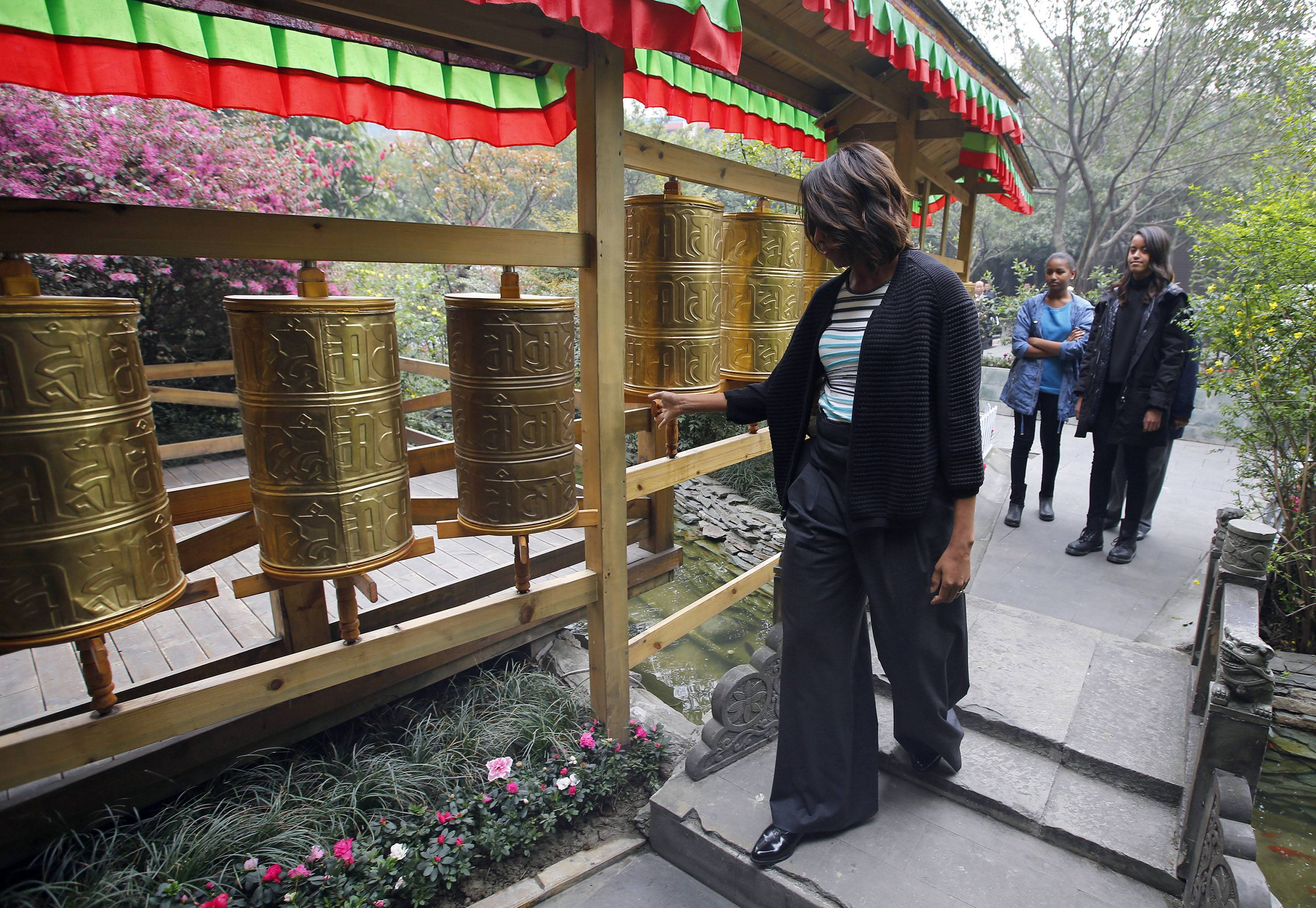 U.S. first lady Michelle Obama, left, touches Tibetan prayer wheels as her daughters Malia, right, and Sasha watch outside a Tibetan restaurant in Chengdu, Sichuan province, China Wednesday, March 26, 2014.