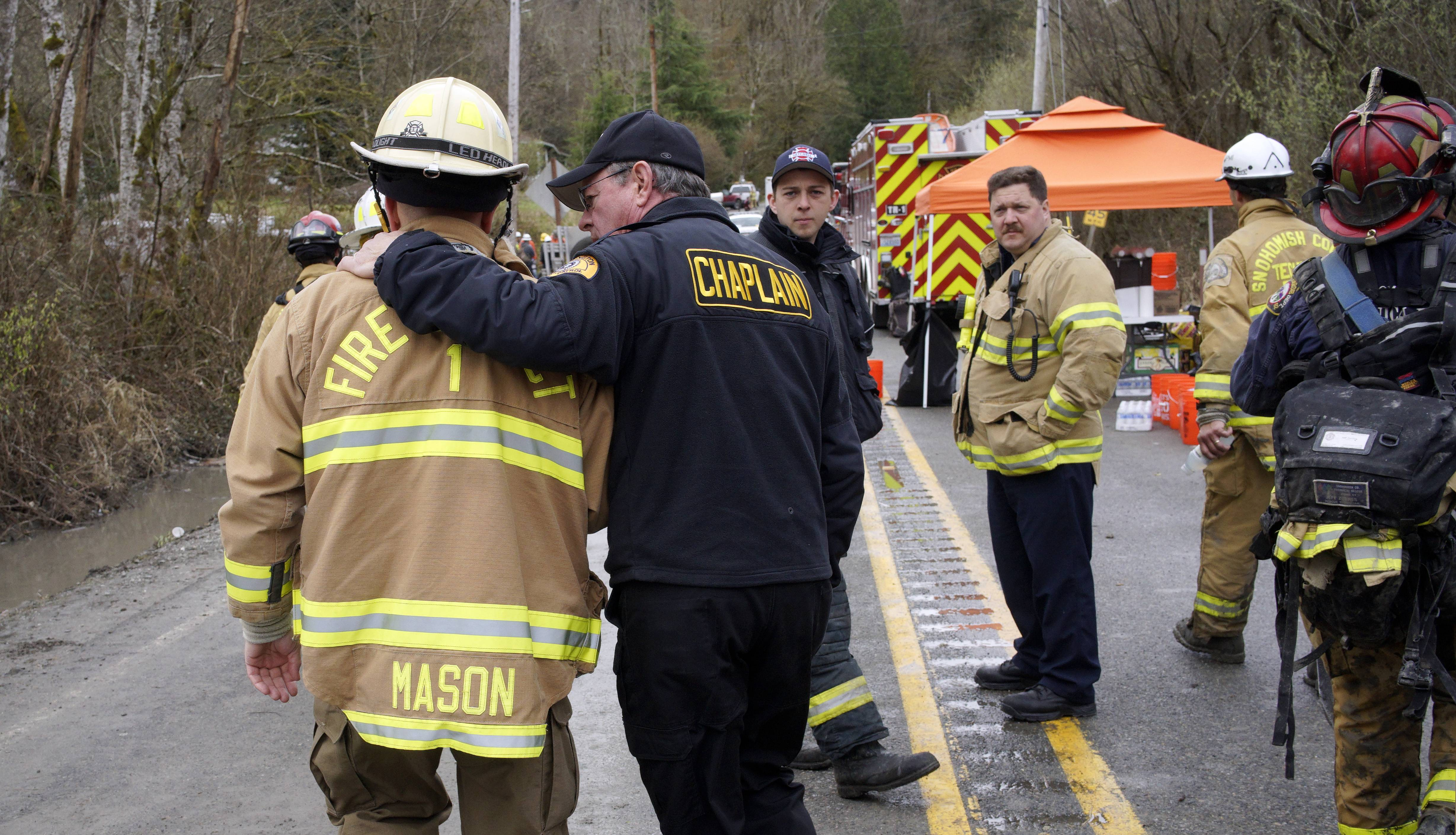 A chaplain from the Washington State Patrol, right, walks with his arm around Snohomish County battalion chief Steve Mason near the scene of the mudslide Wednesday in Oso, Wash. Sixteen bodies have been recovered, and scores of others are still missing.