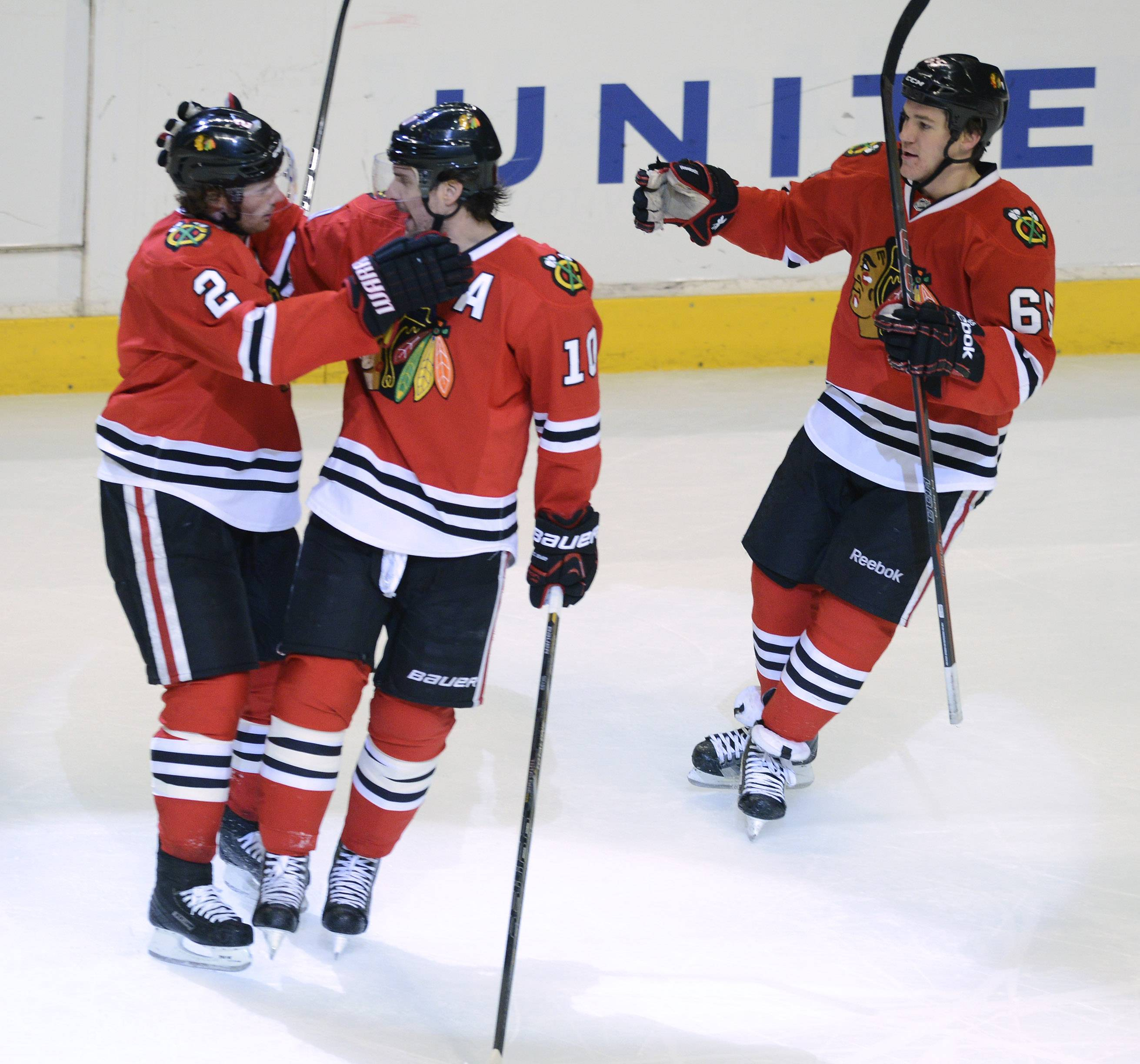 Duncan Keith, left, celebrates his second-period goal with teammates Patrick Sharp, middle, and Andrew Shaw during Tuesday's 4-2 victory over the Stars.