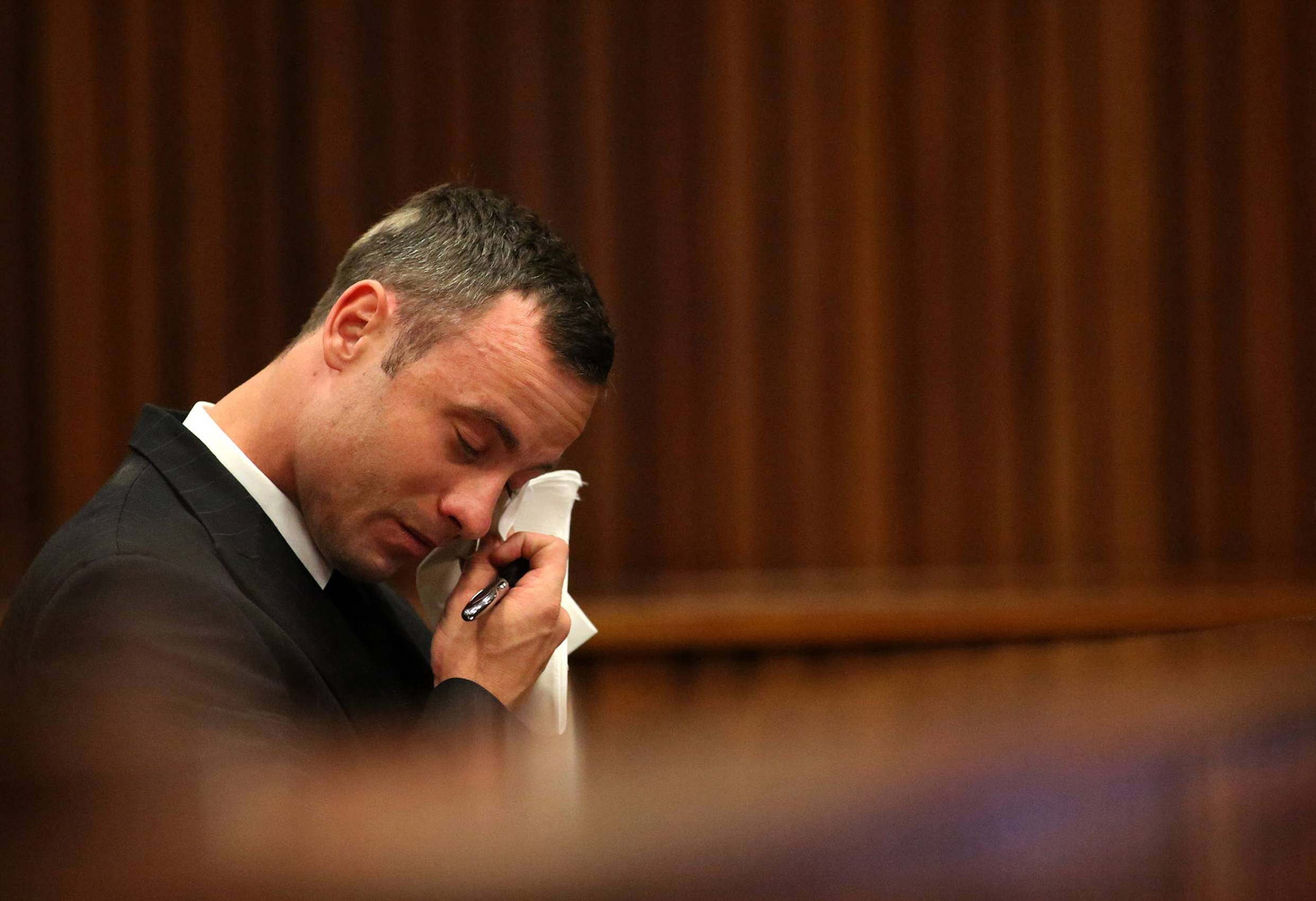 Oscar Pistorius reacts in the dock during cross questioning on mobile phone text messages between him and Reeva Steenkamp in court in Pretoria, South Africa, Tuesday, March 25, 2014. Pistorius is charged with the Valentines Day 2013 shooting death of his girlfriend Reeva Steenkamp. (AP Photo/Siphiwe Sibeko, Pool)