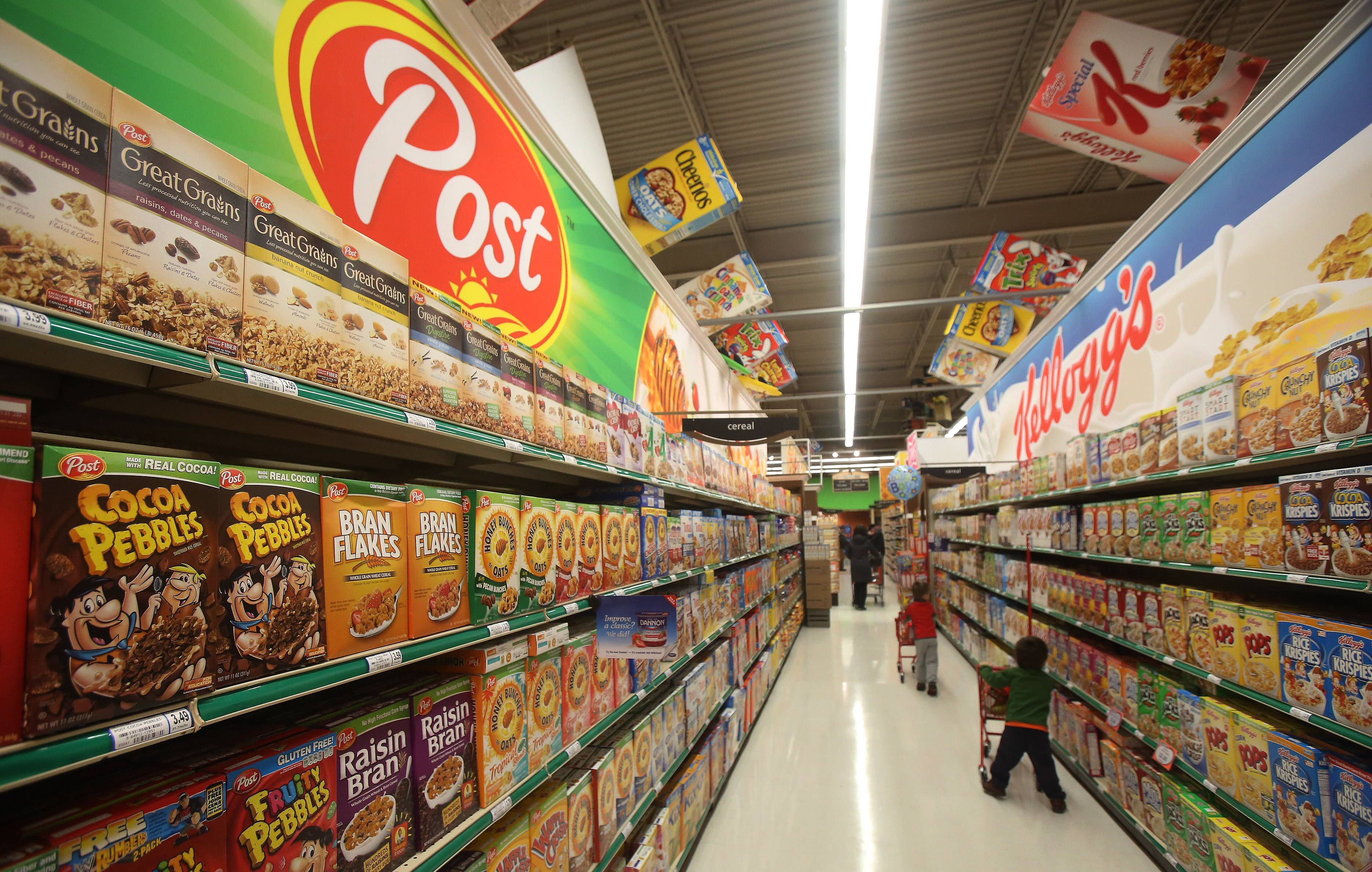 Children walk down the cereal aisle looking at the big signs.