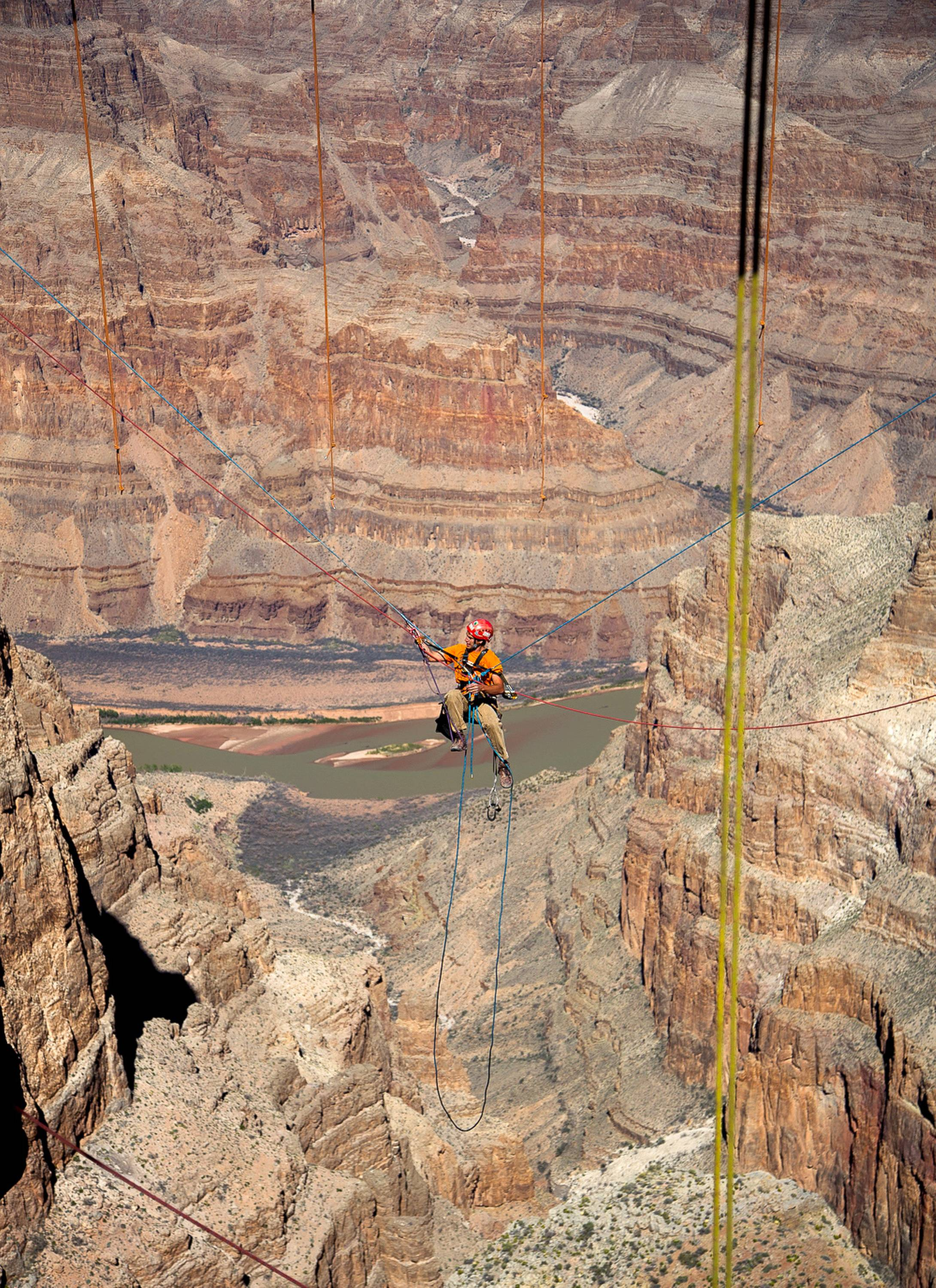 A technician dangles from a series of ropes before polishing the underside glass at Grand Canyon Skywalk in Hualapai Reservation, Ariz.