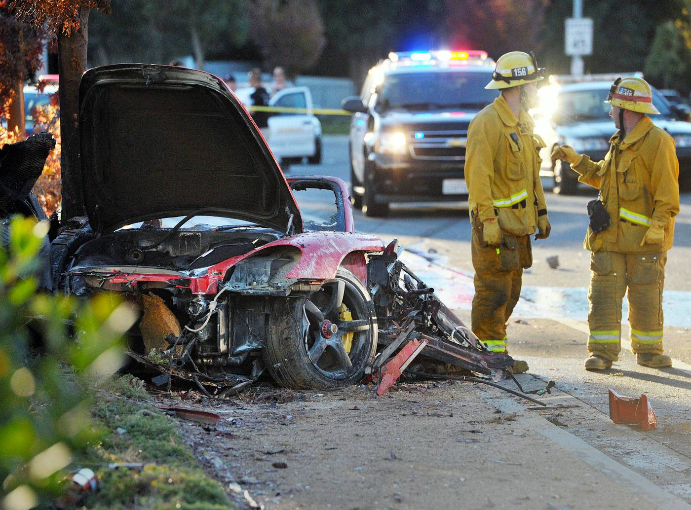 Firefighters work next to the wreckage of a Porsche that crashed into a light pole killing actor Paul Walker and his friend Roger Rodas in Valencia, Calif. Crash investigators have determined that the Porsche was traveling up to 94 mph when it went out of control.