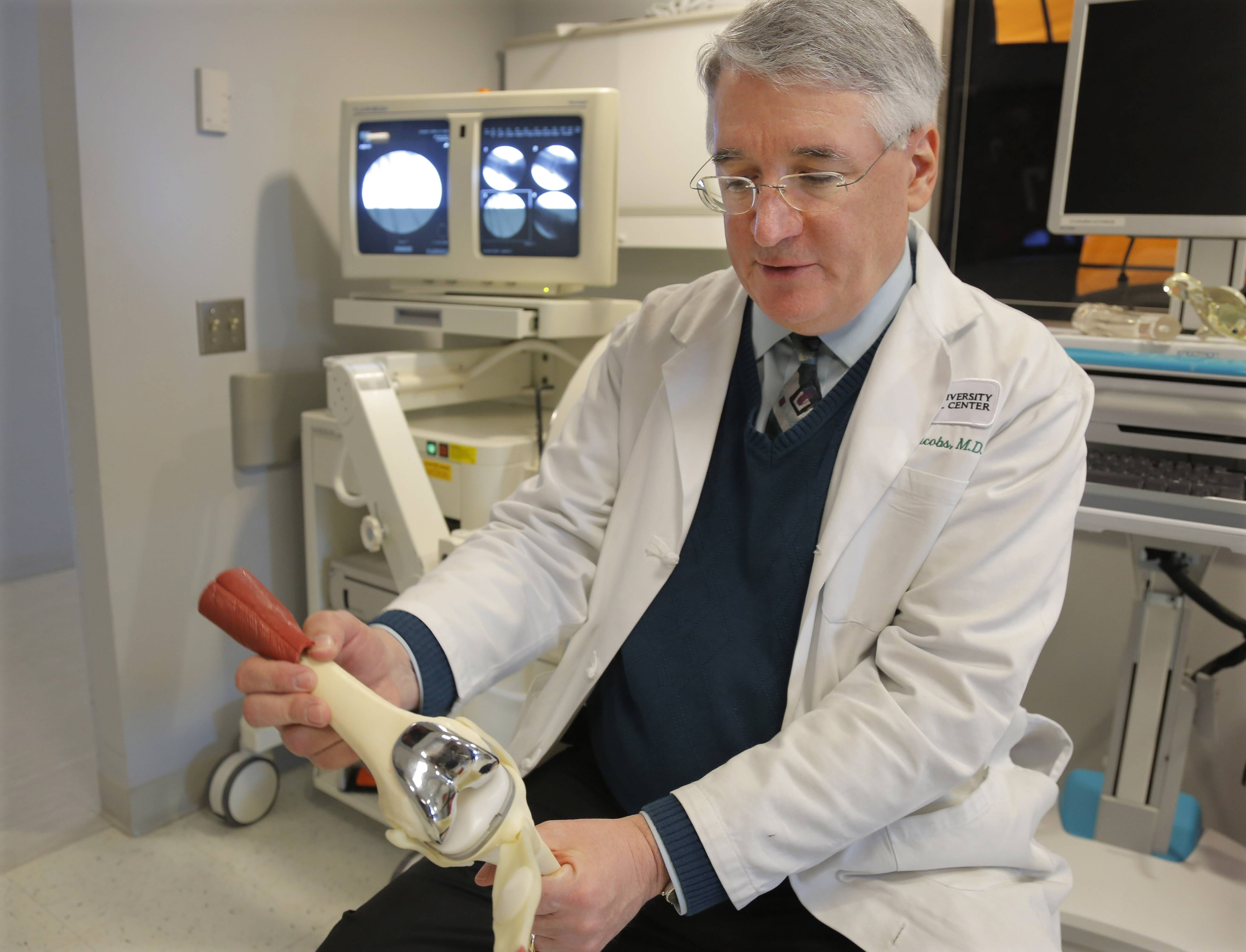Dr. Joshua Jacobs, orthopedics surgery chief at Rush University Medical Center and president of the American Academy of Orthopaedic Surgeons in Chicago, holds a model of a tri-compartmental total knee replacement. About two of every 100 Americans now has an artificial joint, doctors are reporting.