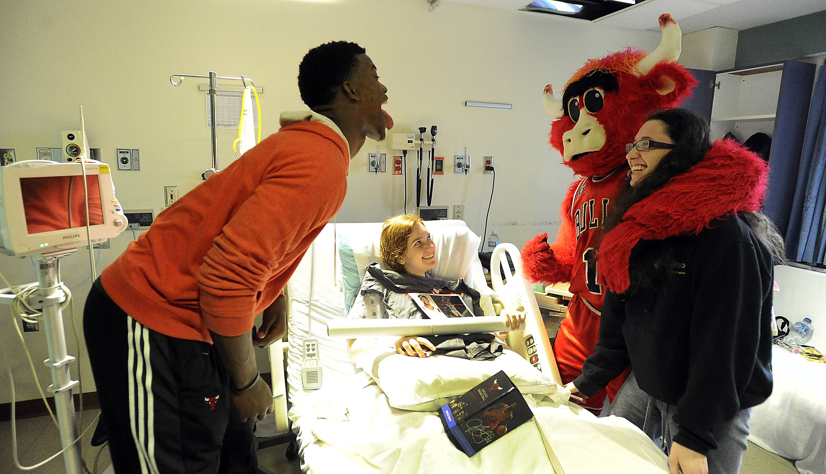 Mark Welsh/mwelsh@dailyherald.comChicago Bulls guard Jimmy Butler and team mascot Benny the Bull visits with Michelle Katz, 15, of Buffalo Grove and her sister Rachel, 16, at Lutheran General Advocate Children's Hospital in Park Ridge on Thursday.