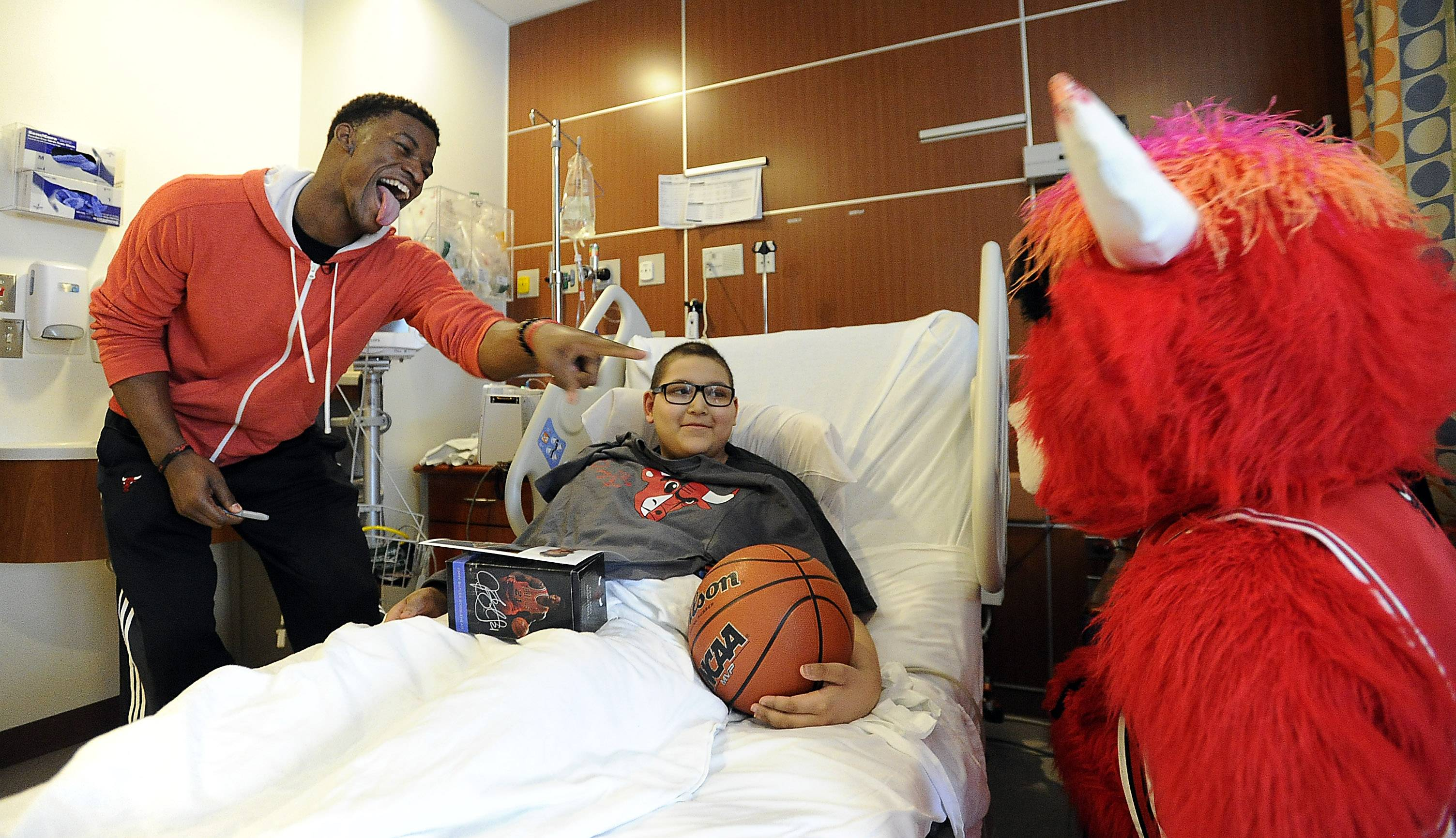 Mark Welsh/mwelsh@dailyherald.comChicago Bulls guard Jimmy Butler and team mascot Benny the Bull visits with Miguel Arizmendi, 10, at Lutheran General Advocate Children's Hospital in Park Ridge on Thursday.