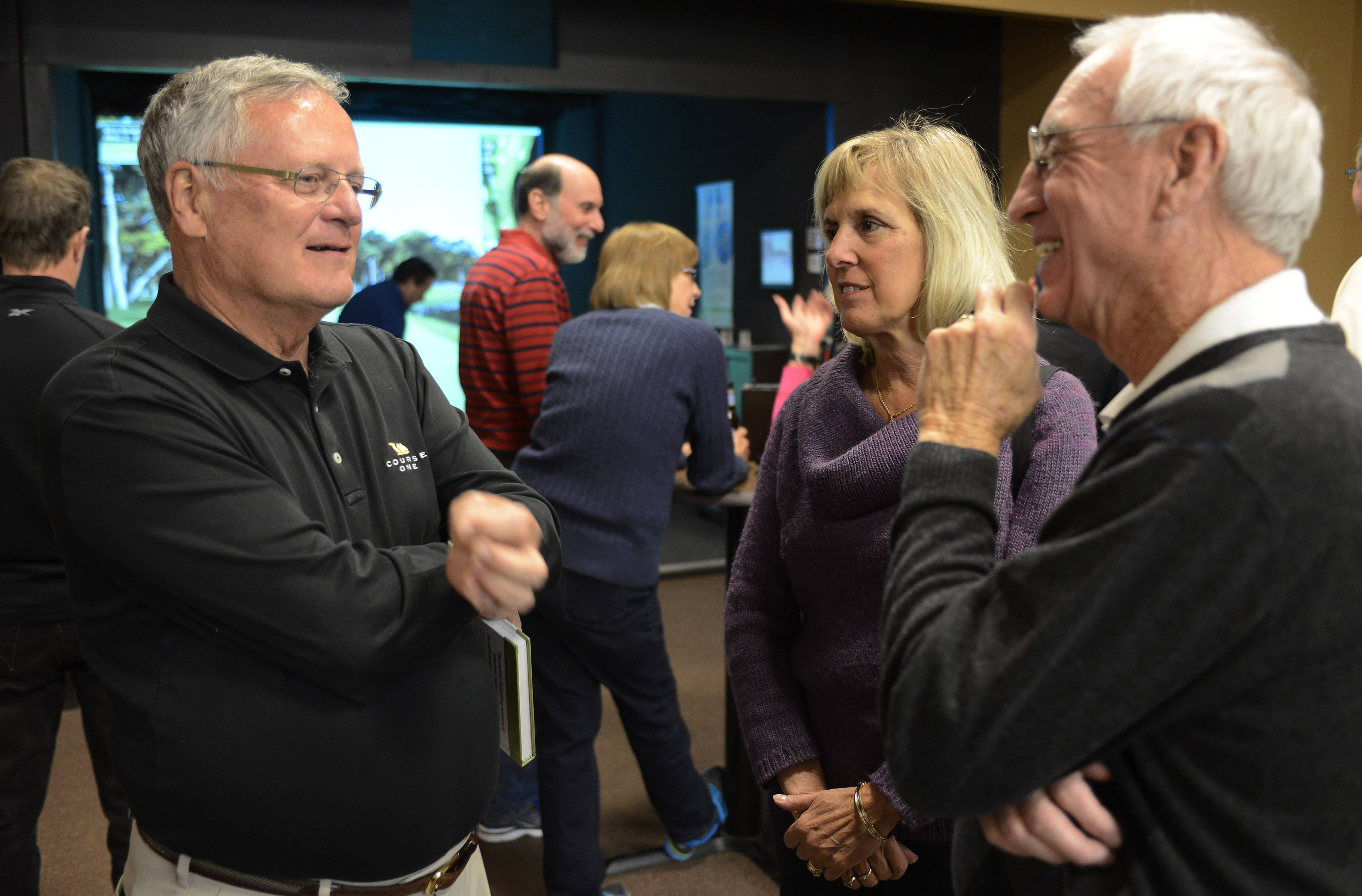Veteran golf writer Len Ziehm, left, chats with Mary and Mike Bavier of Barrington during an event for Daily Herald subscribers Wednesday at Golf Nation in Palatine.
