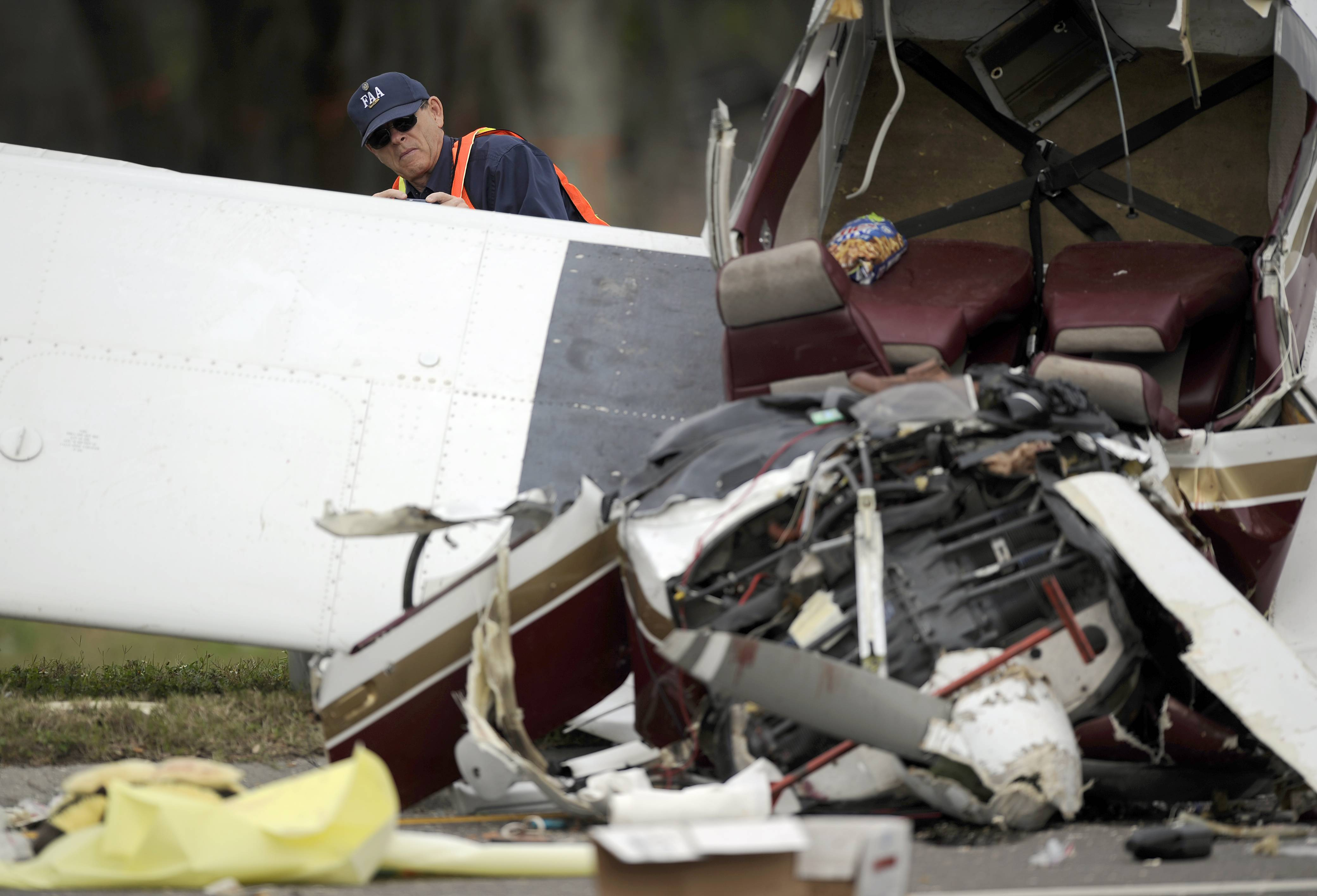 An investigator from the FAA takes photographs of a small passenger plane that crashed early Saturday in Clearwater, Fla. Authorities say the single-engine plane crashed at about 4 a.m. Saturday in Clearwater.