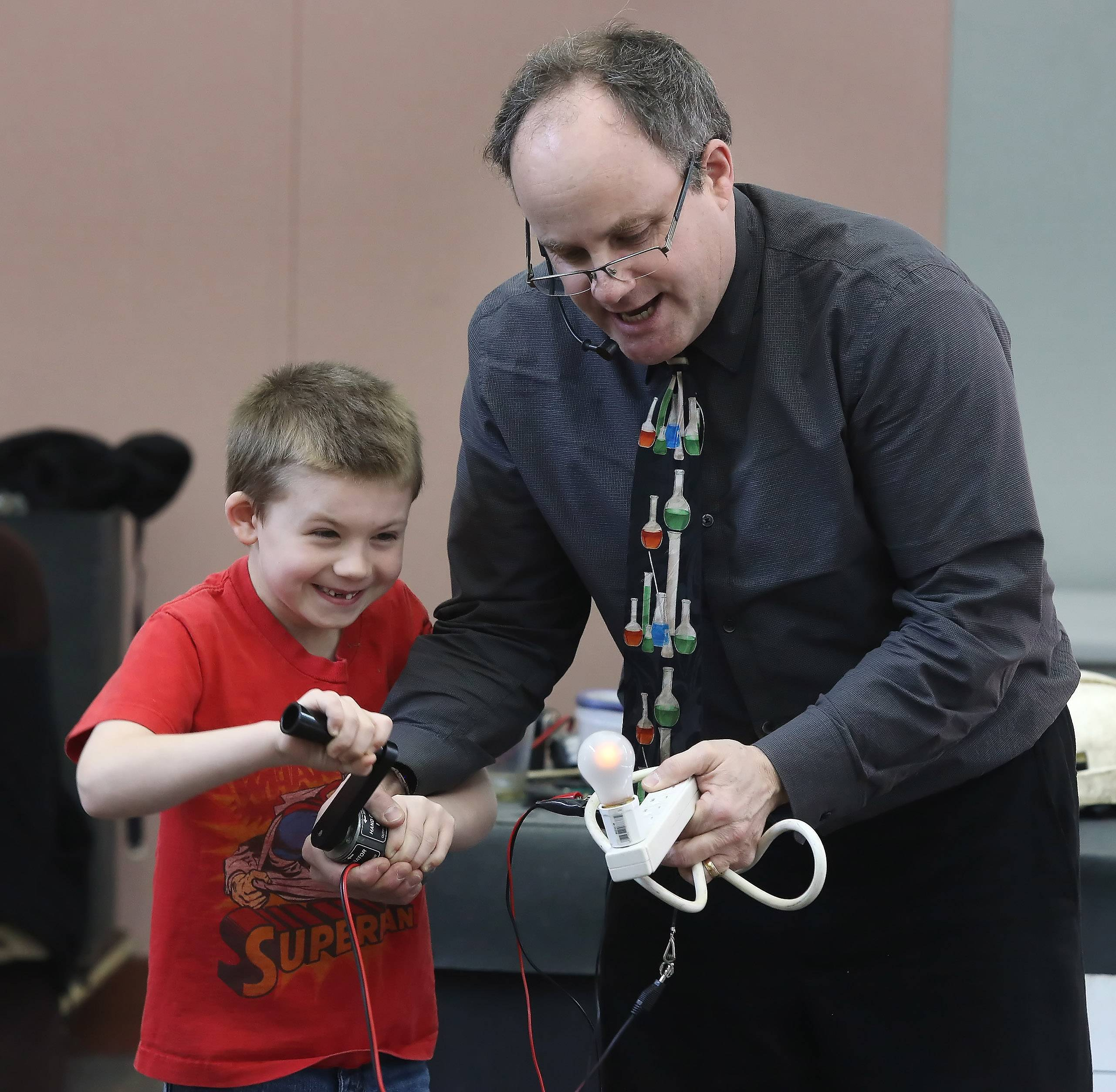 "Engineer Steve Belliveau works with T.J. Stites, 6, of Lake Villa, as they create electricity to turn on a light bulb during the ""Getting Excited About Science"" program Wednesday at Lake Villa District Library. Belliveau used demonstrations and humor to illustrate scientific concepts."