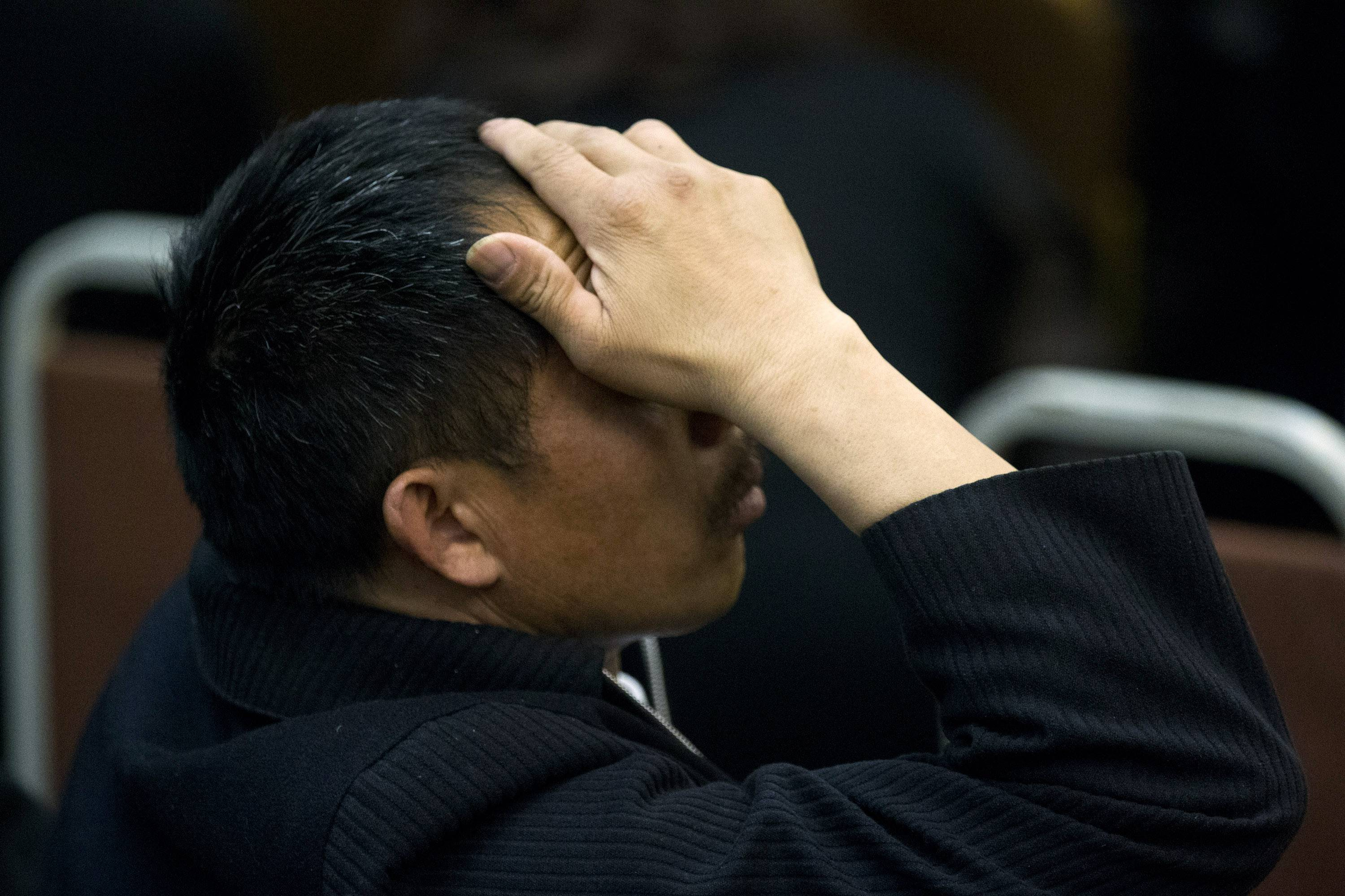 One of the relatives of Chinese passengers on board Malaysia Airlines Flight 370 rubs his head during a briefing meeting given by Malaysian official at a hotel in Beijing, China, Wednesday, March 26, 2014.