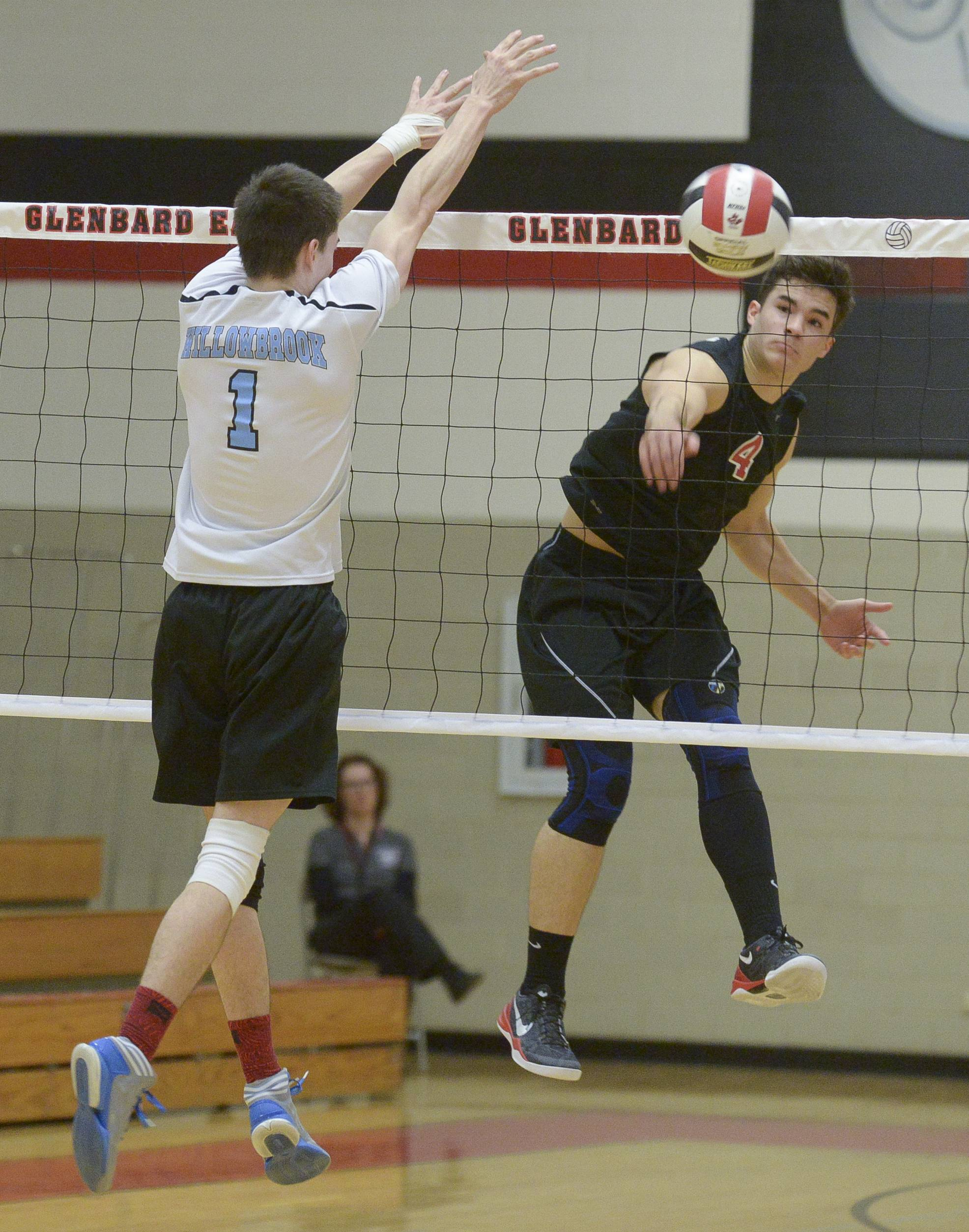 Glenbard East's Sterling Glover fires one past Willowbrook's Ryan Wakely during in boys varsity volleyball in Lombard Wednesday.