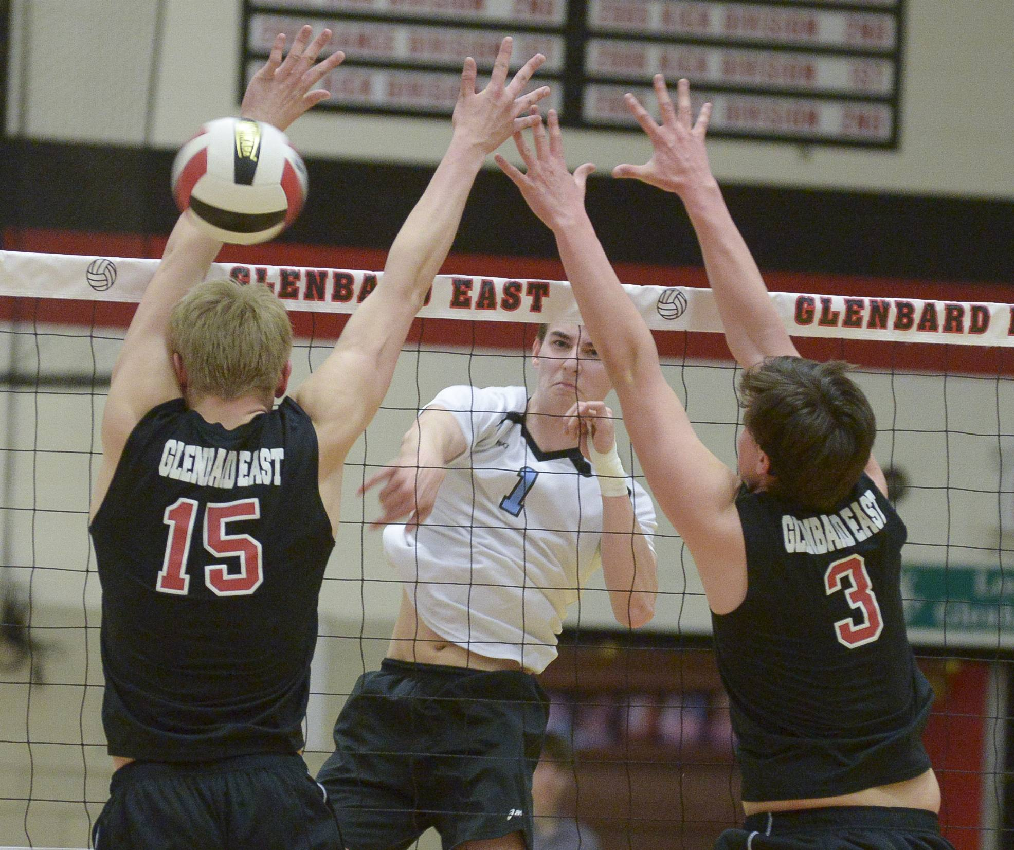Willowbrook's Ryan Wakely fires one past Glenbard East's Erik Fiebrandt and Alex Bojan during in boys varsity volleyball in Lombard Wednesday.