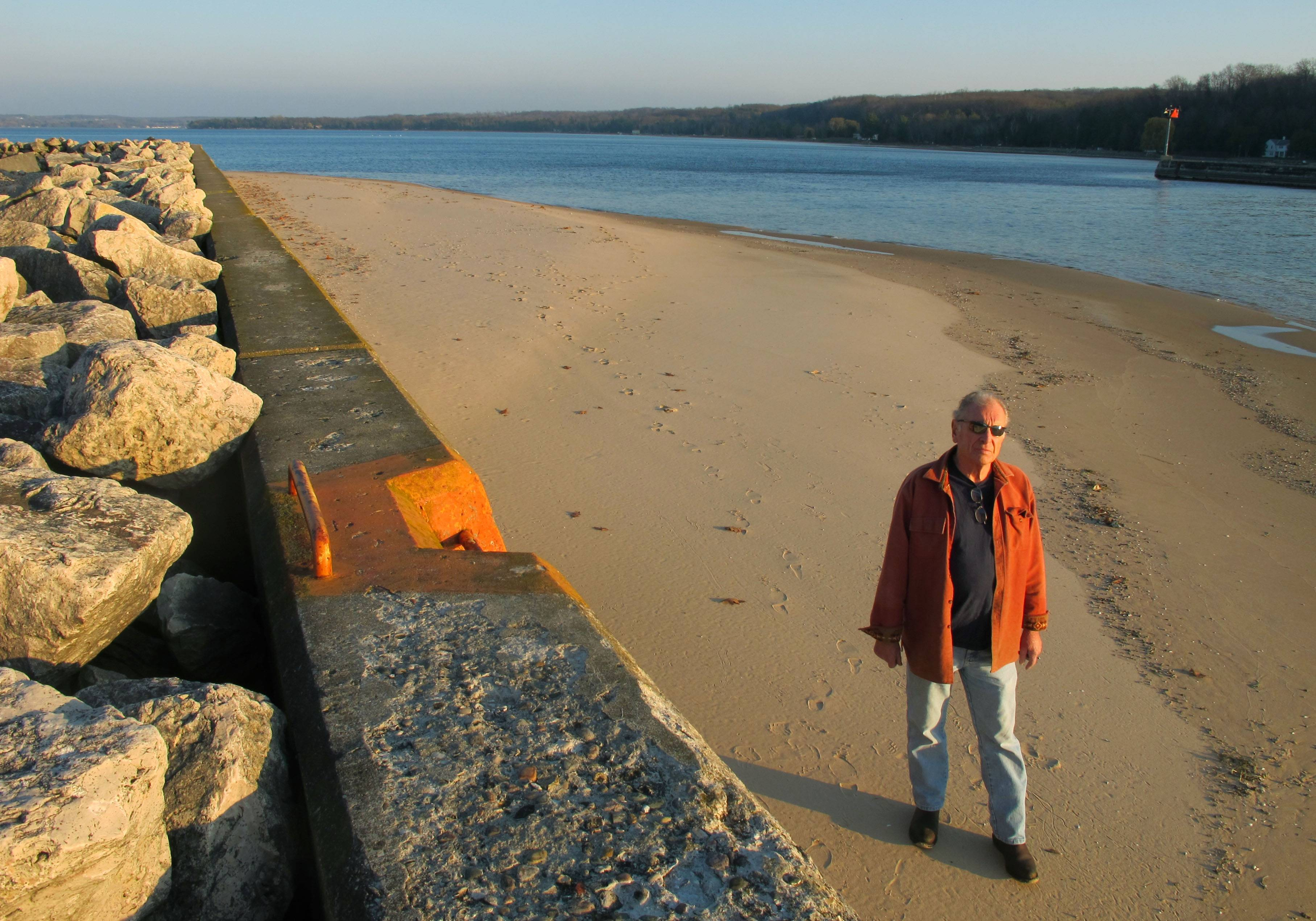 Jim Simons walks along a sand bar, exposed by low water levels on the Portage Lake channel that leads to Lake Michigan at Onekama, Mich. University of Michigan scientists will conduct a wide-ranging study on how Great Lakes communities can adapt to fluctuating water levels.