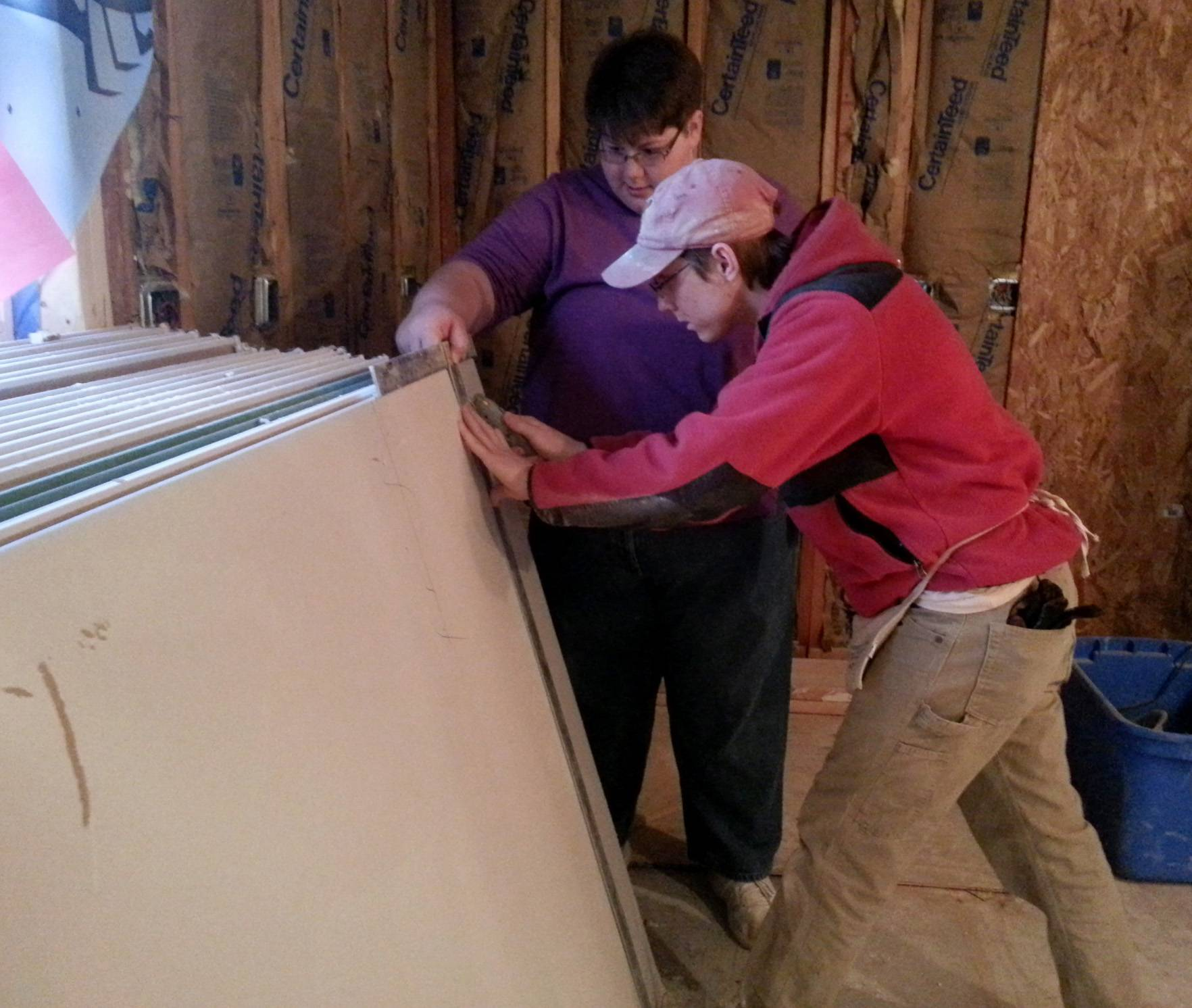 Jason Bauer and Megan Kathka cut drywall that is being installed this week at a Habitat for Humanity home in Carpentersville. A group of 10 Elgin Community College students participated in an Alternative Spring Break program offering students a chance to volunteer in the community for course credit.