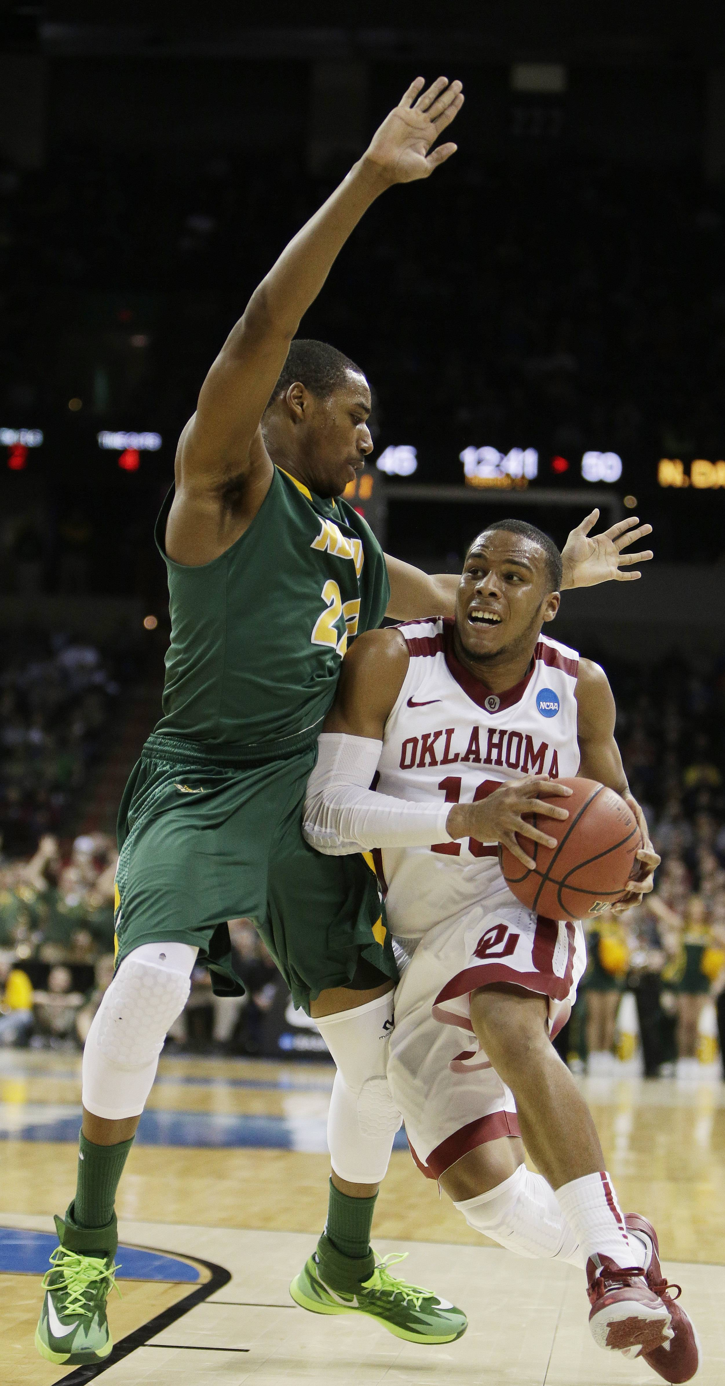 Oklahoma's Jordan Woodard (10) drives against North Dakota State's Kory Brown (22), an Elgin High graduate, in the second half of a second-round game of the NCAA Tournament in Spokane, Wash., last week.