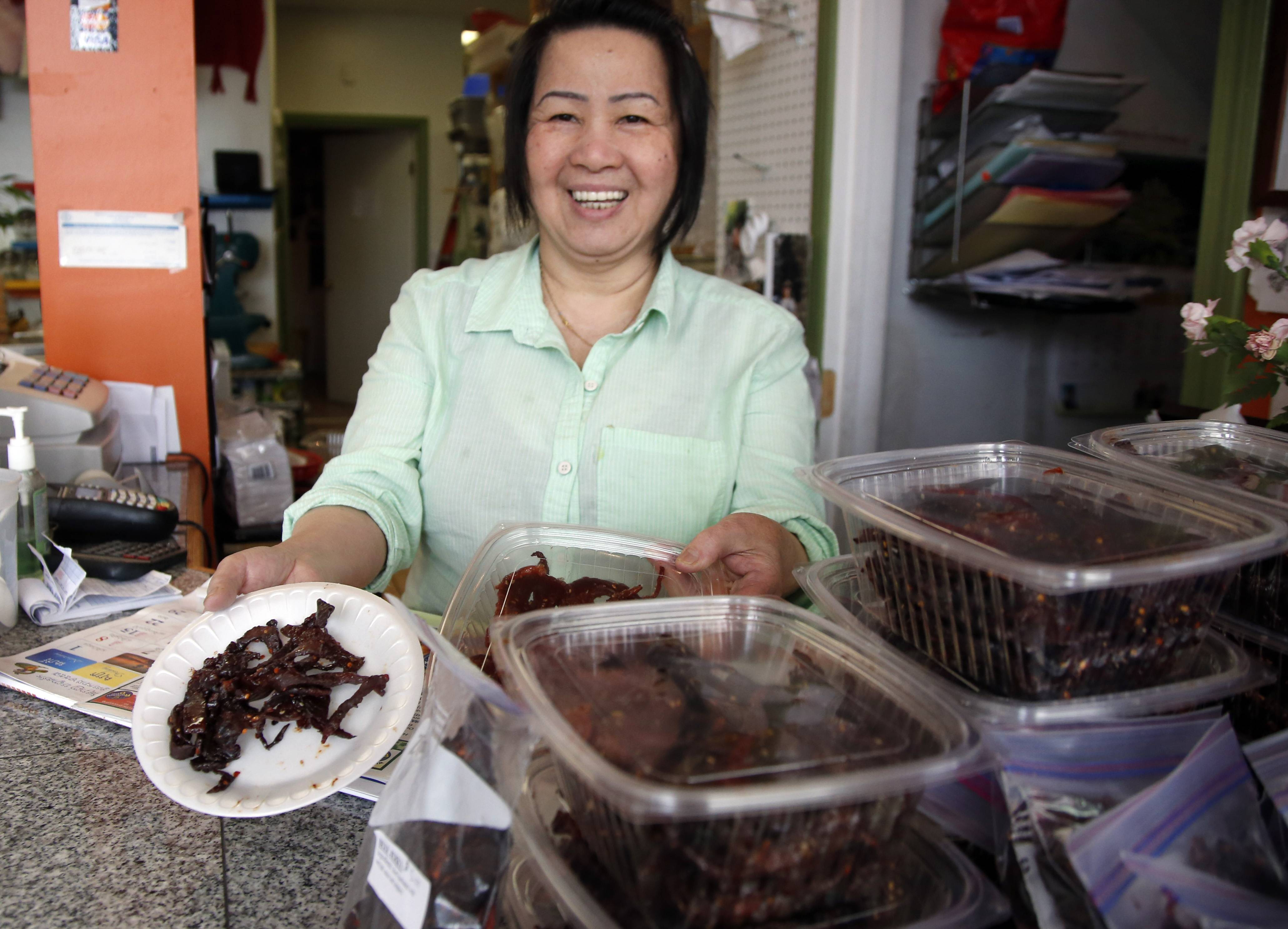 Kimheng Chou shows off her homemade beef jerky at the Dessert Shop and Bakery in Lowell, Mass.